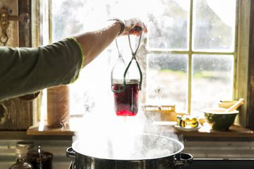 Filled canning jar held above boiling water