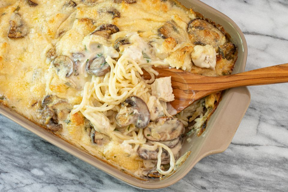 Chicken tetrazzini casserole in baking dish with spoon.