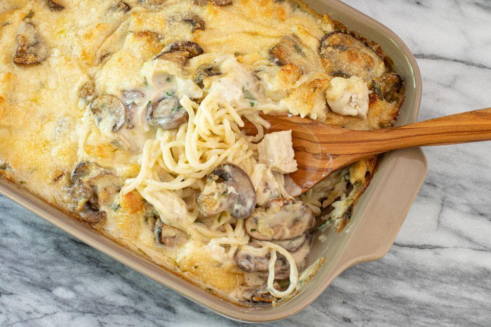 Chicken tetrazzini casserole in baking dish with spoon.