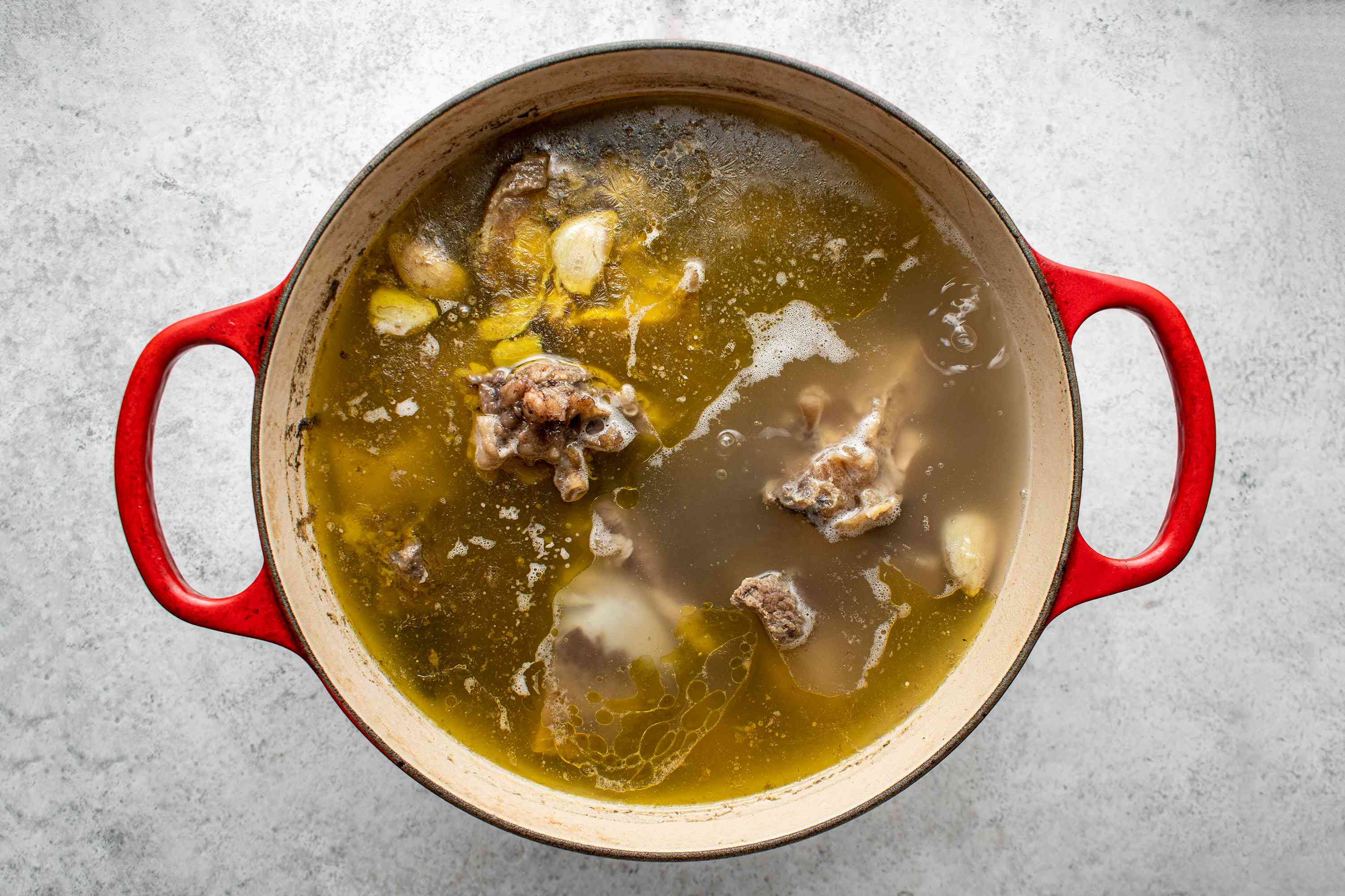 Add the ginger, garlic, cinnamon, cardamom, cloves, and peppercorns to the bones in the pot
