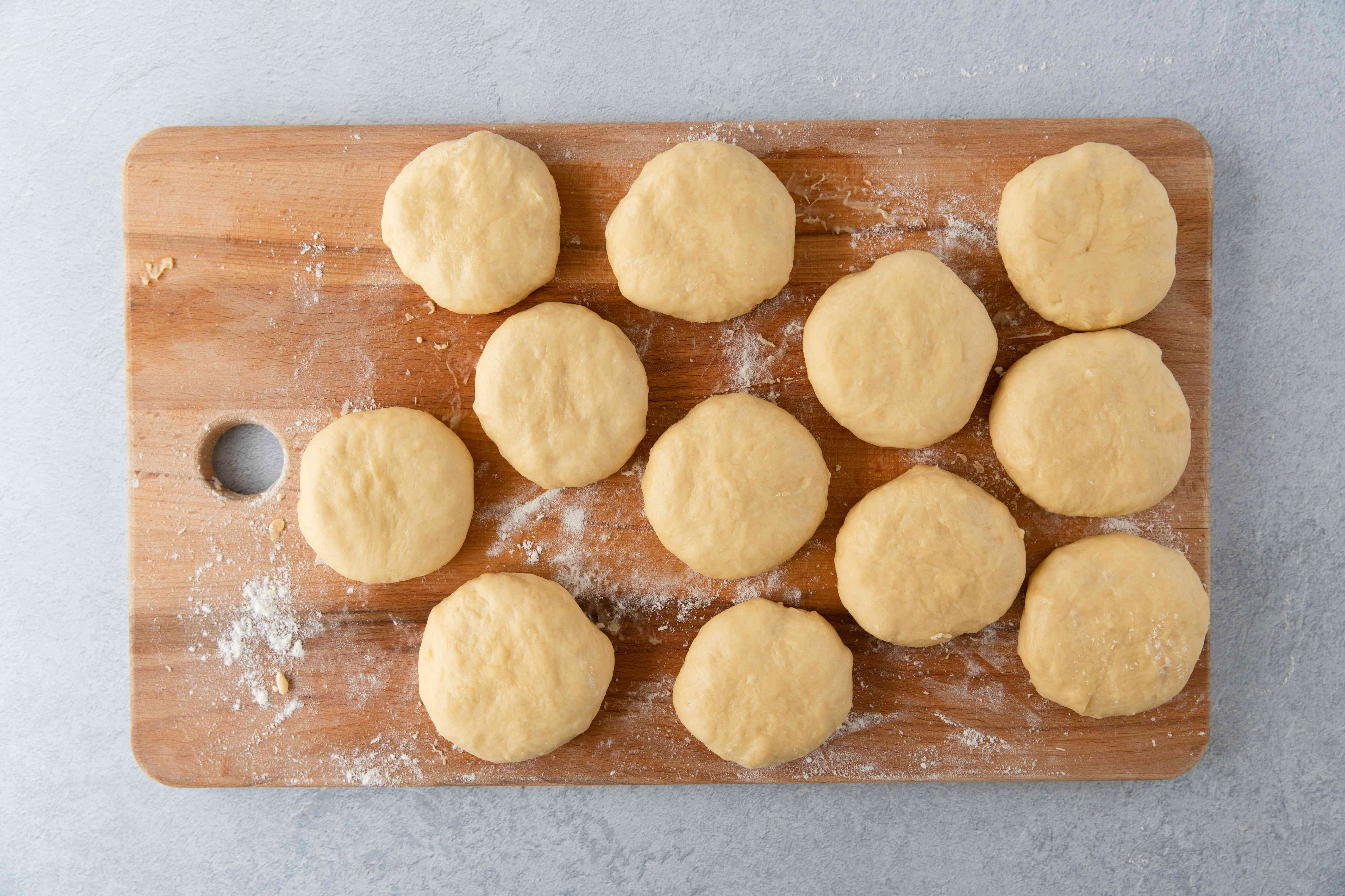 Dough balls shaped into thick disks on a wooden cutting board