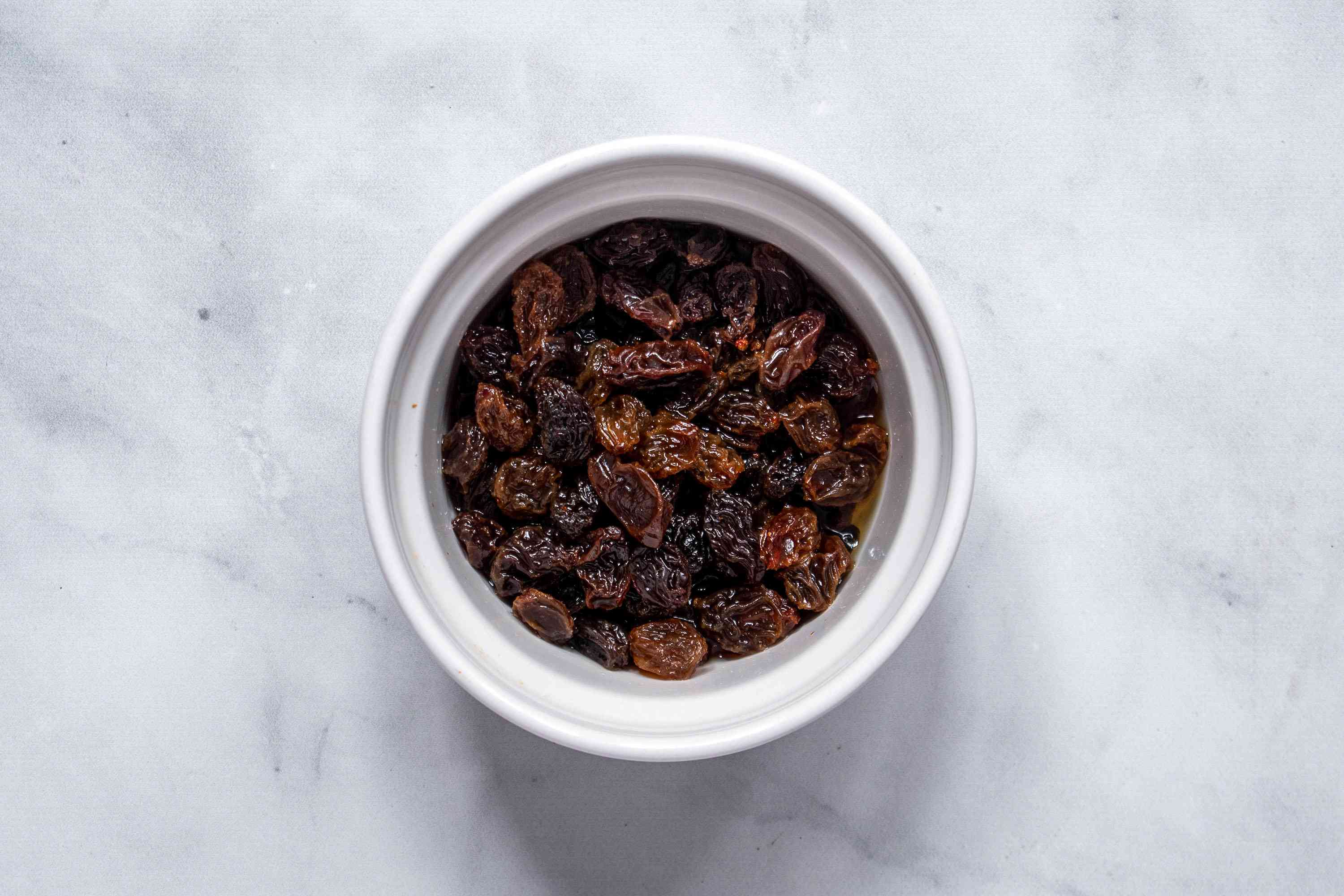 Raisins soaked in rum in a white bowl