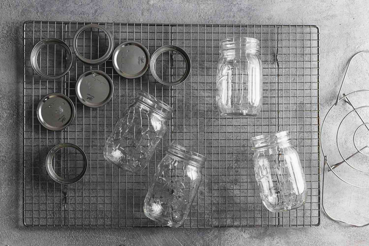 Sterilized glass jars and lids on a metal cooling rack