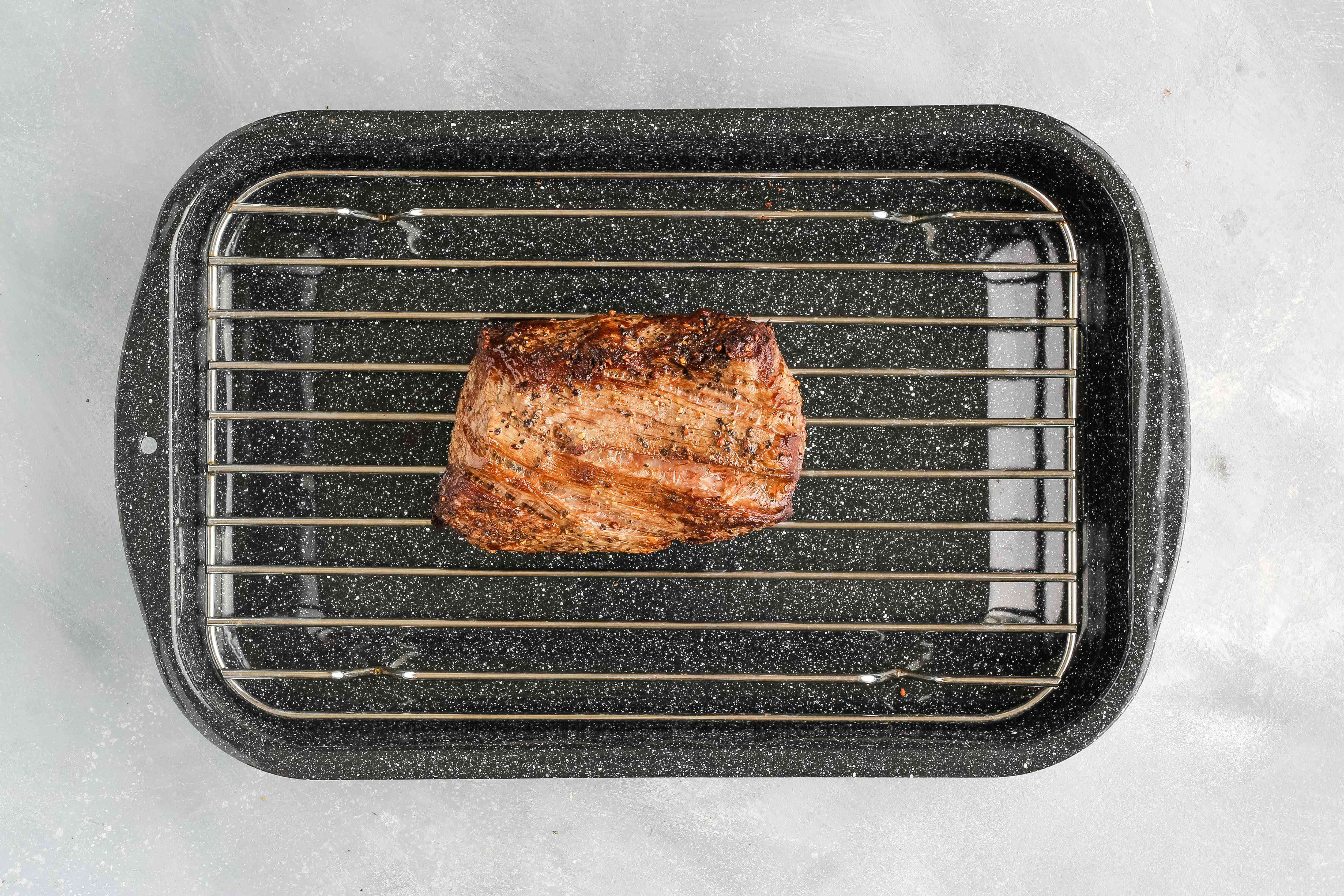 The tenderloin rests on a rack over a roasting pan