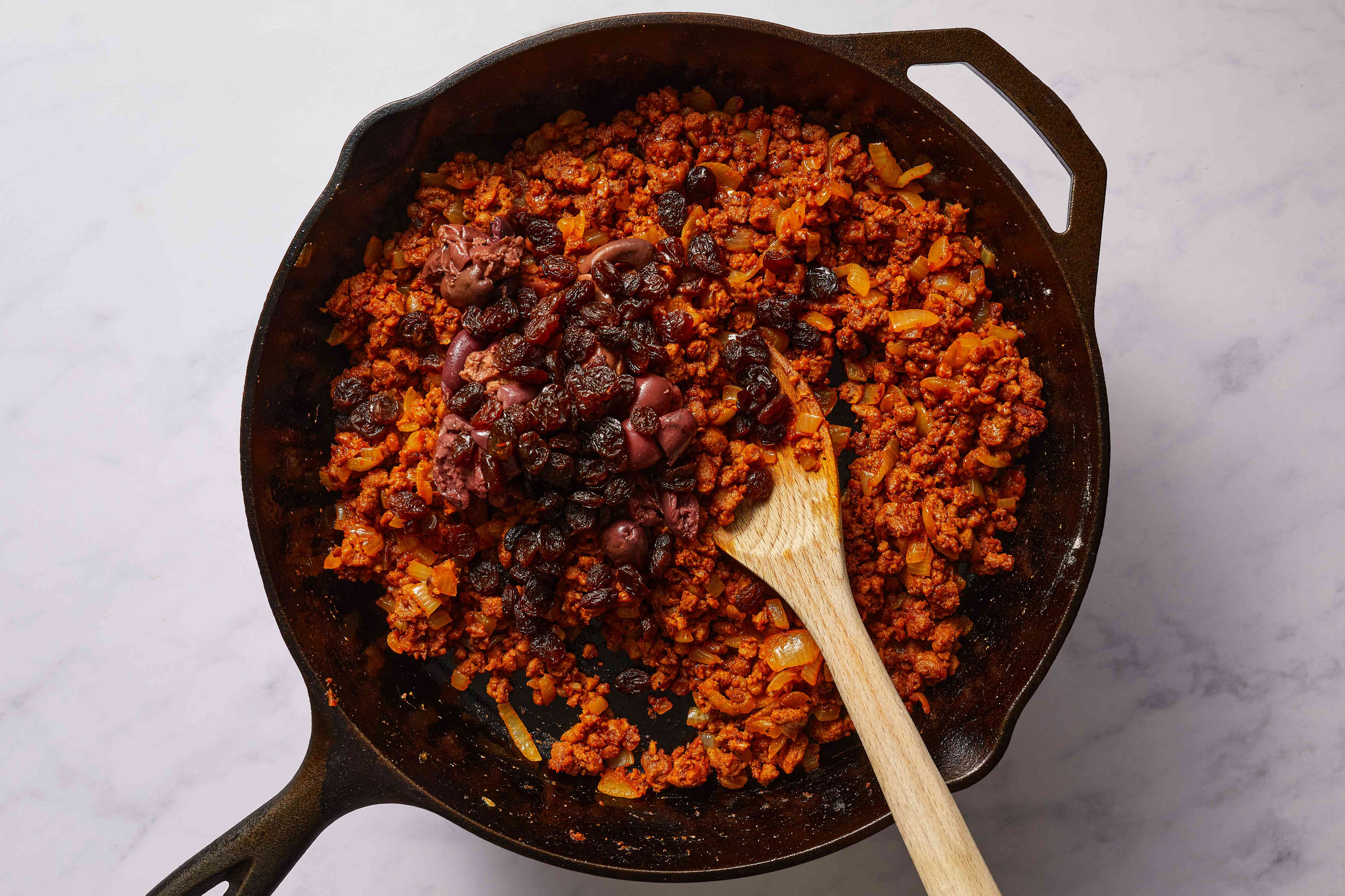 stir the raisins and black olives into the beef mixture in the skillet