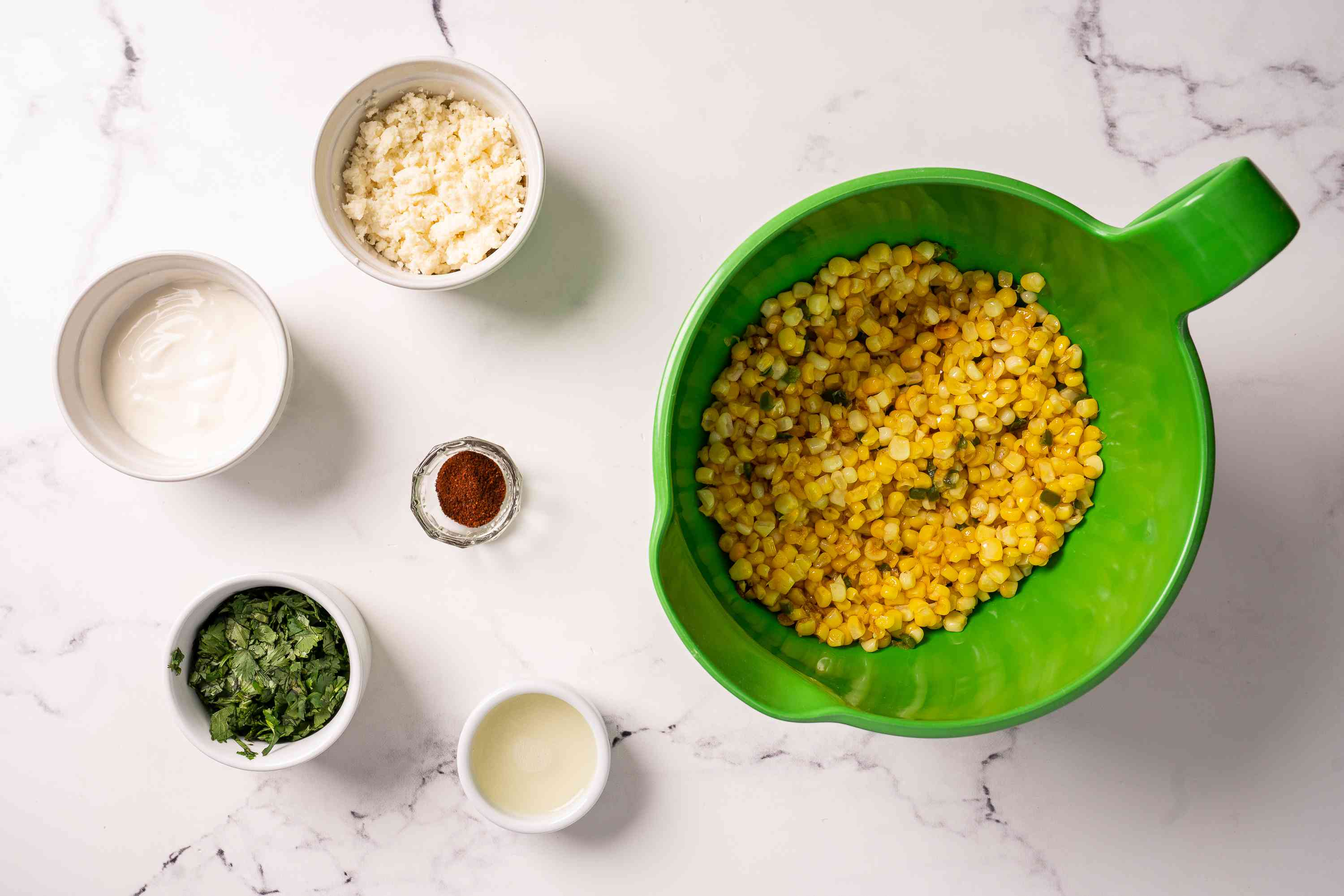 Cooked corn in a bowl with toppings on the side
