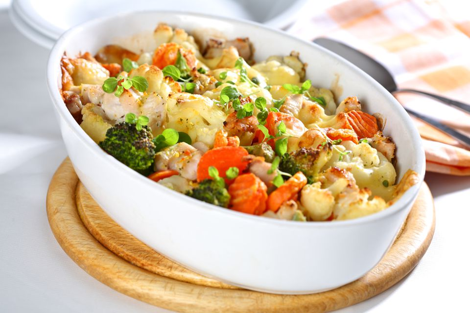 A white dish of baked mixed vegetables on a cutting board