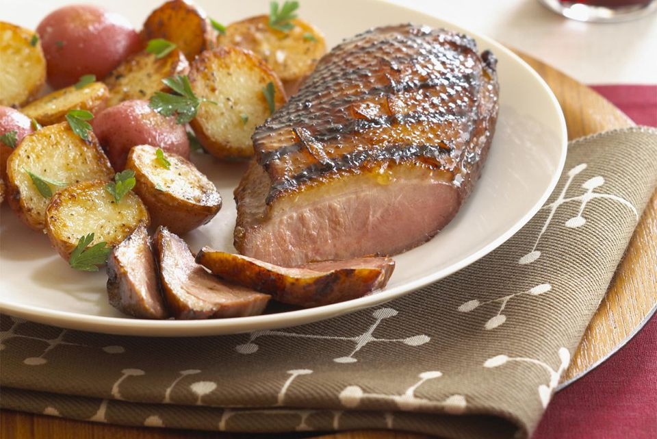 Plate with grilled duck breast, roast potatoes and red wine, close-up