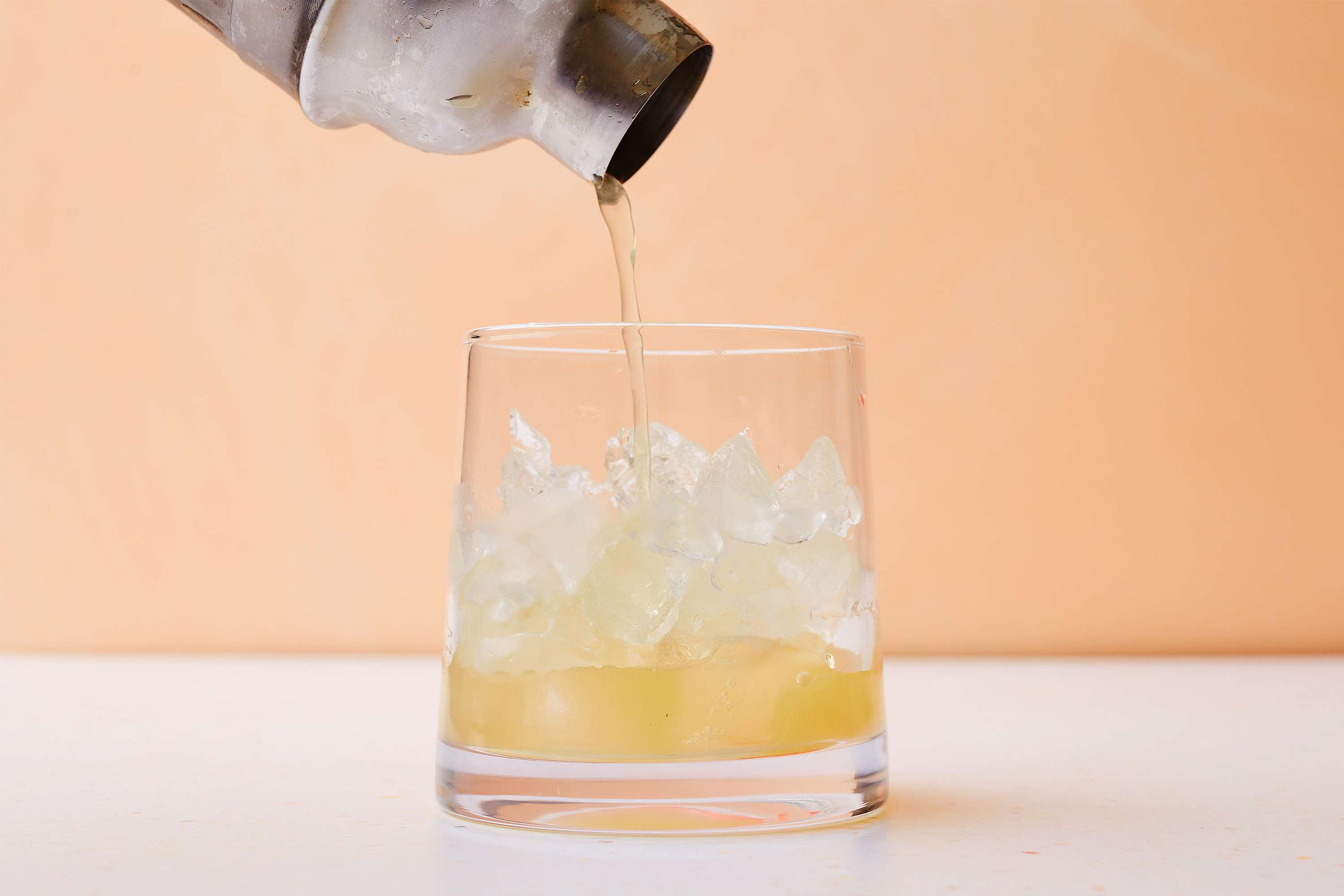 Strain cocktail into a large old-fashioned glass filled with fresh ice