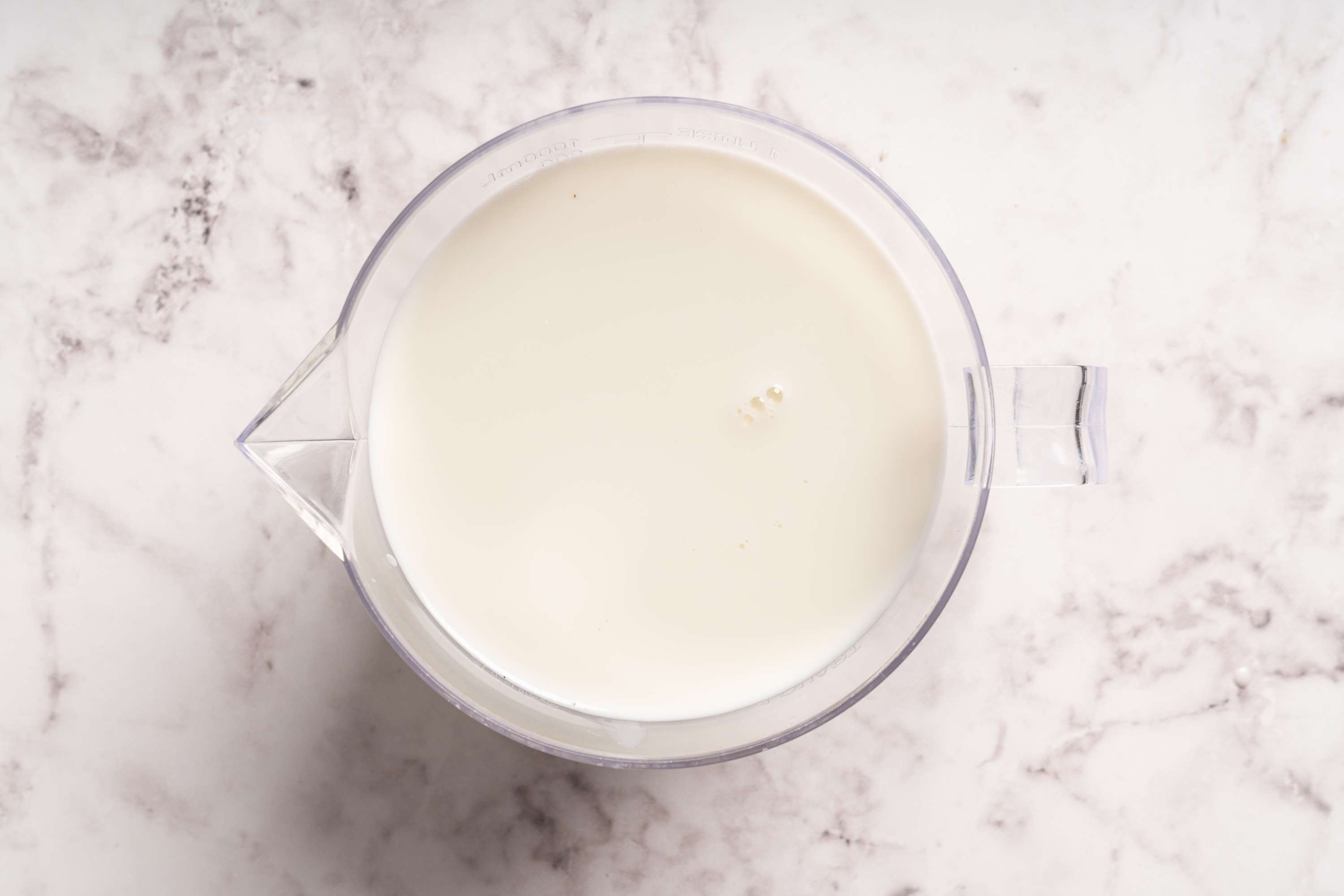 coconut water and milk in a measuring cup