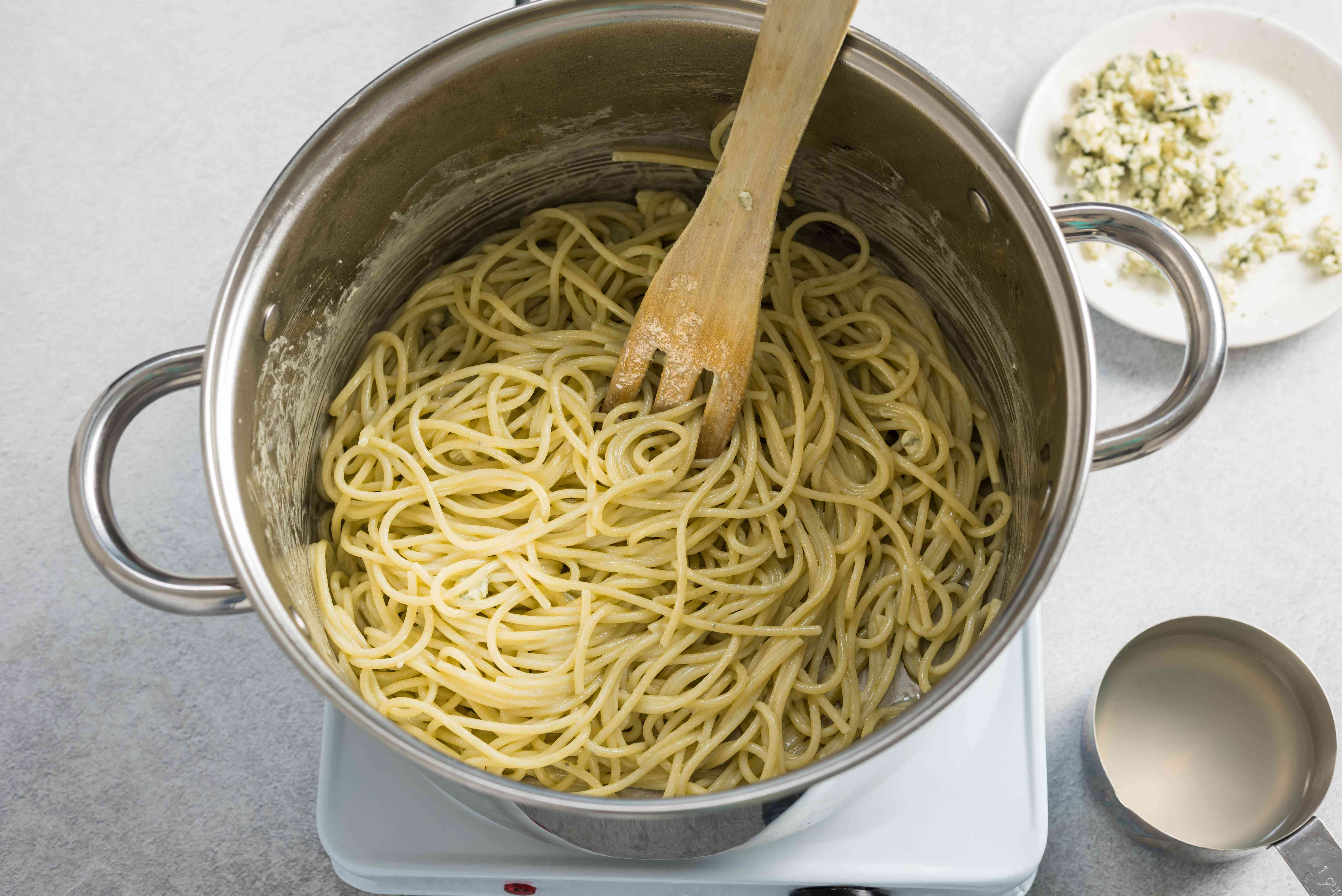 Blue cheese pasta in a pot with pasta water on the side