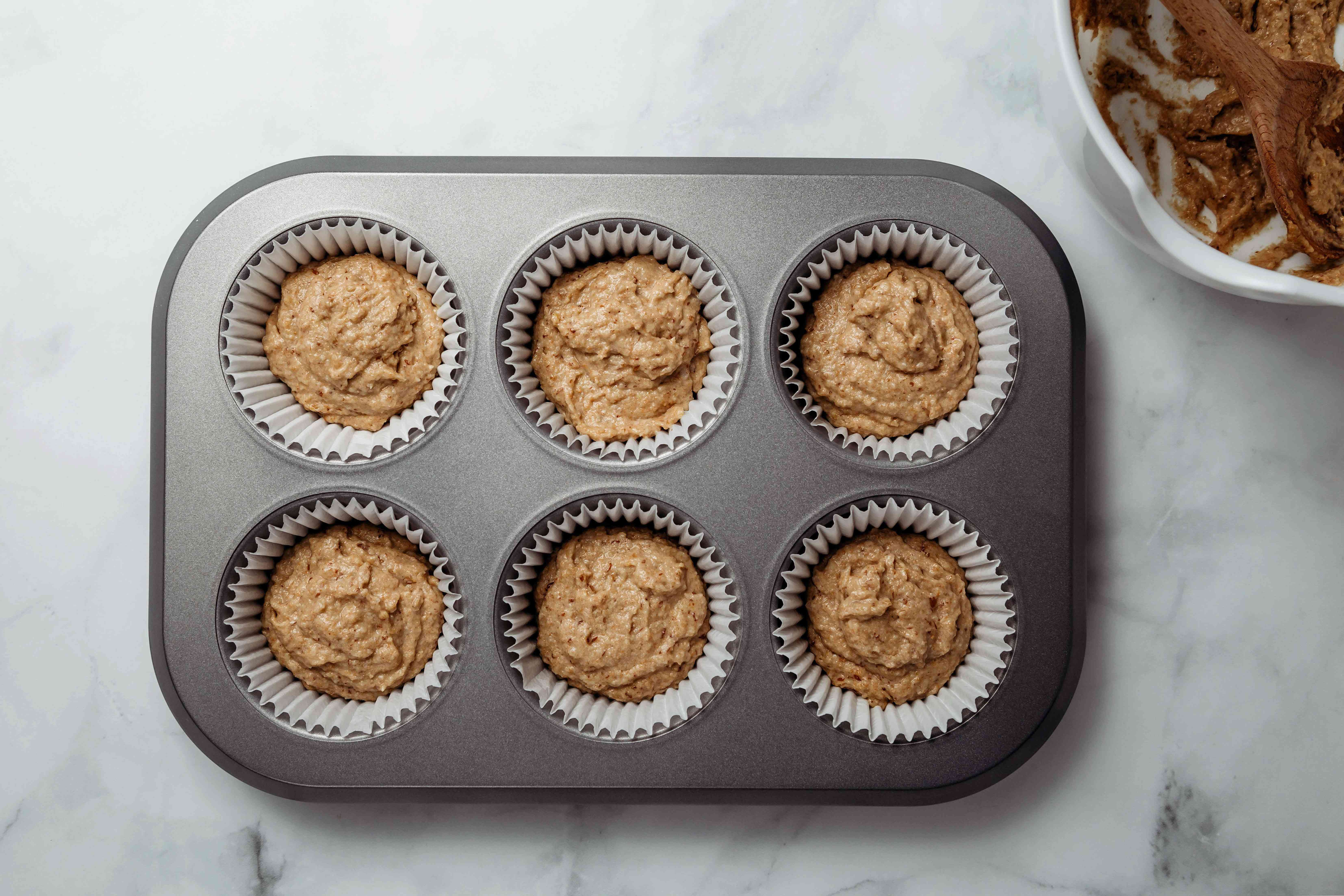 Portion the batter into the prepared muffin pan