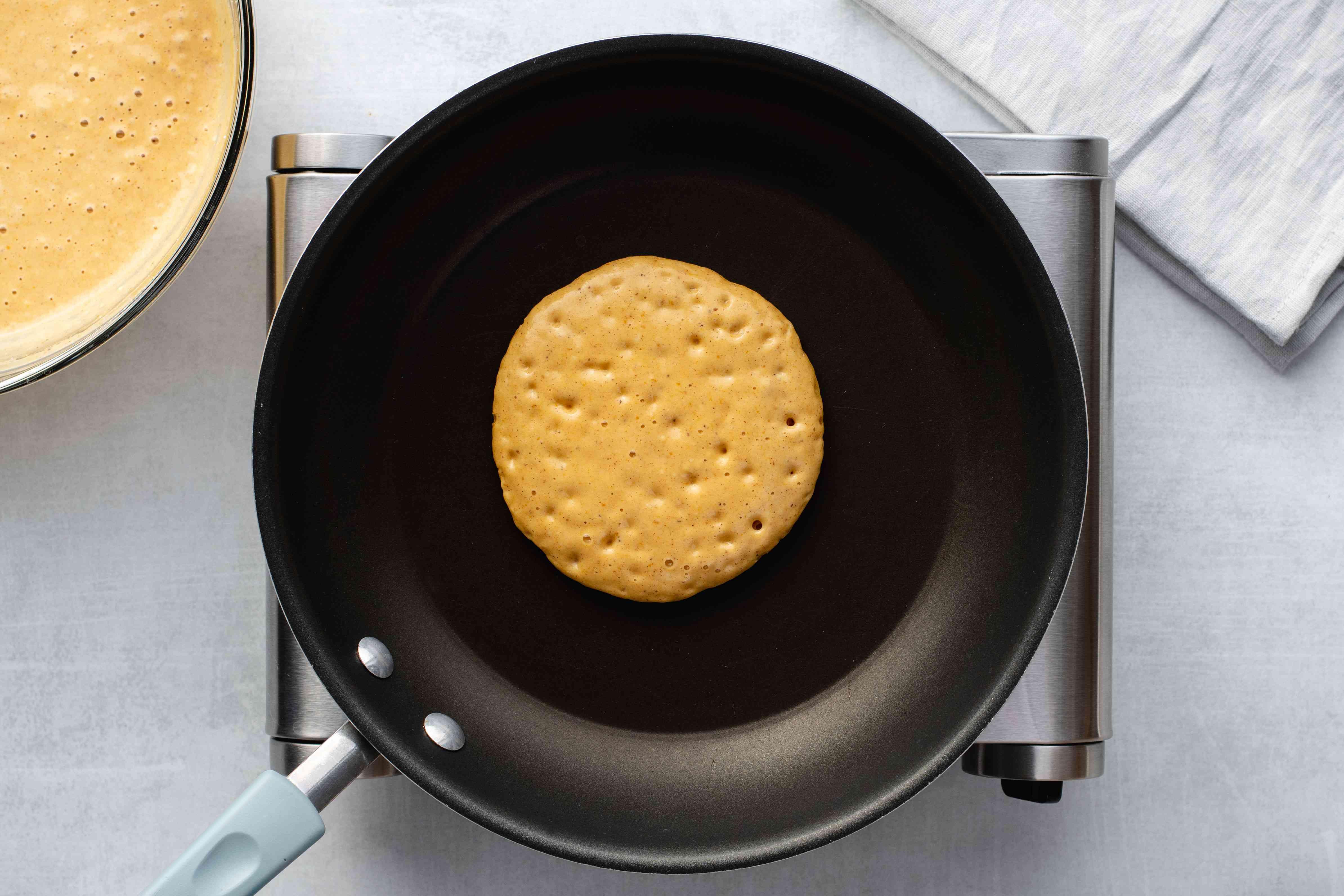 Pumpkin pancake cooking on a pan