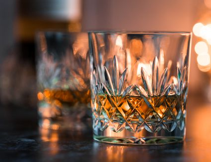 Crystal glasses of whisky on weathered surface - stock photo