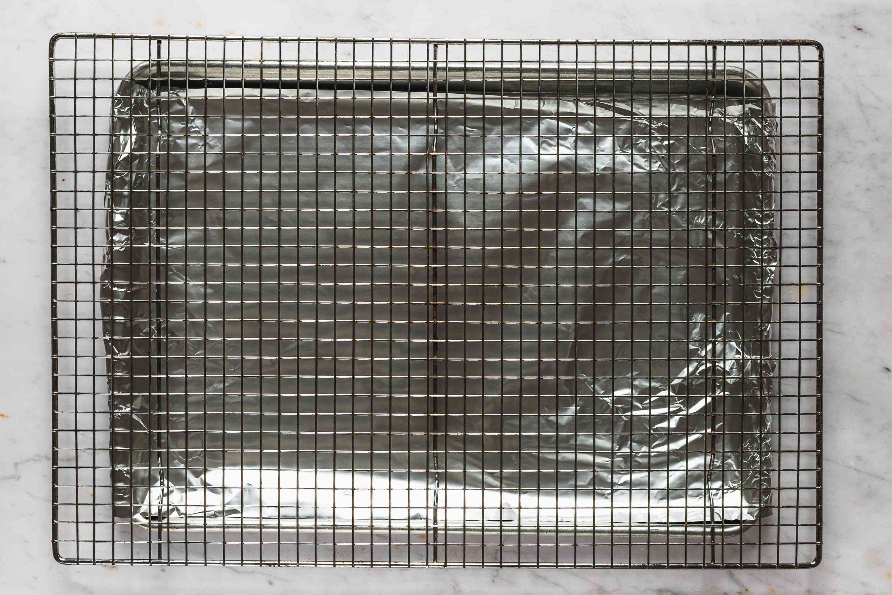 cooling rack on top a of an aluminum foil lined baking sheet
