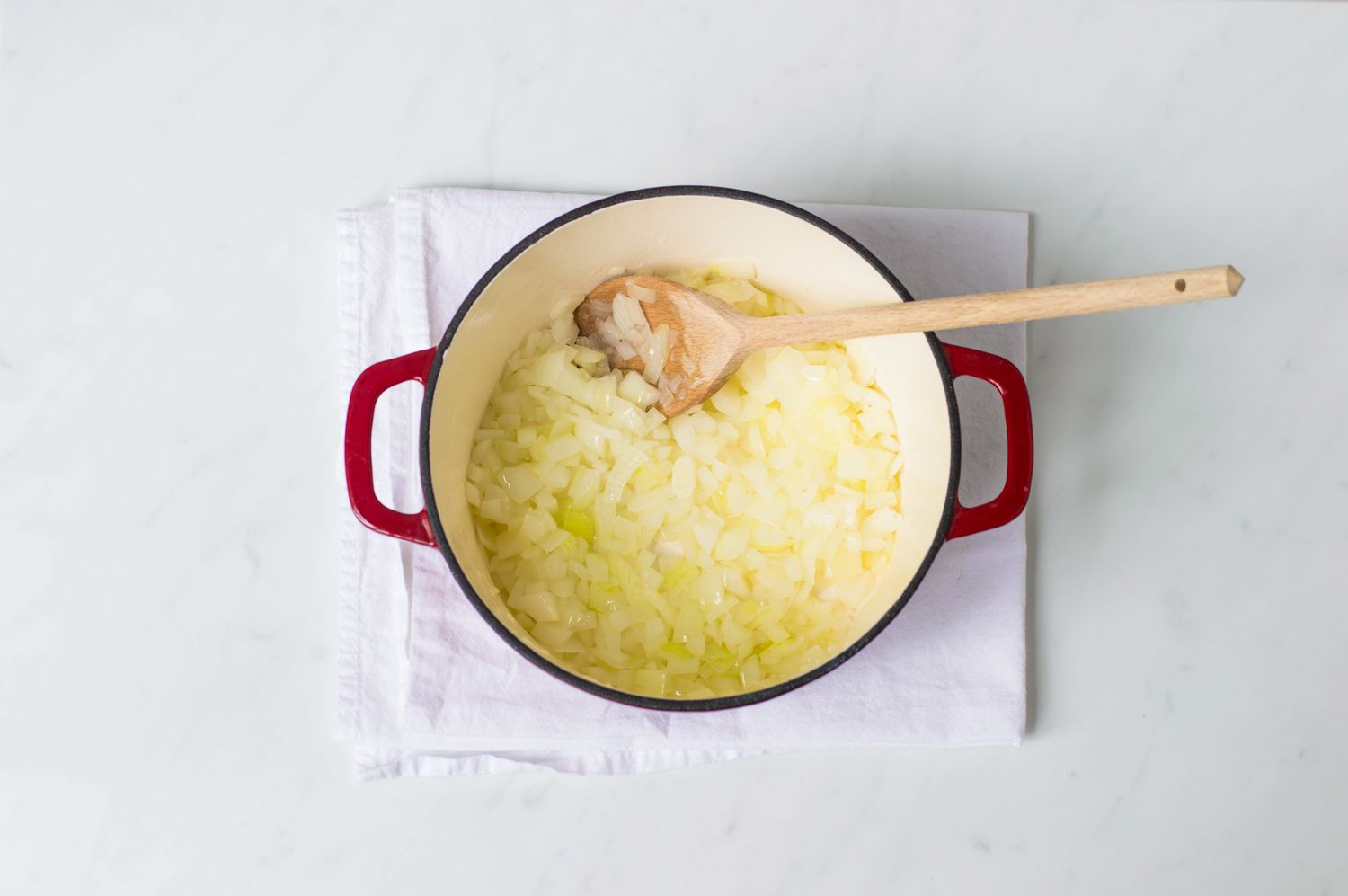 Onions cooking in a Dutch oven with a wooden spoon