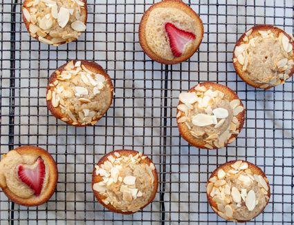Fluffy golden financier tea cake with strawberries and slivered almonds