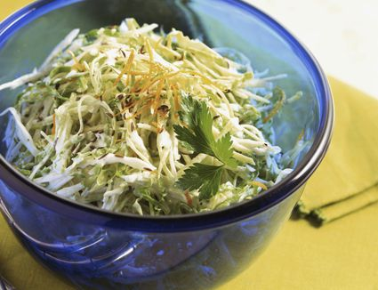 Cold raw cabbage salad in a blue glass bowl
