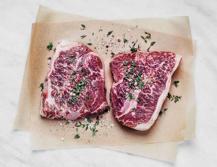 Raw steak seasoned with salt and herbs