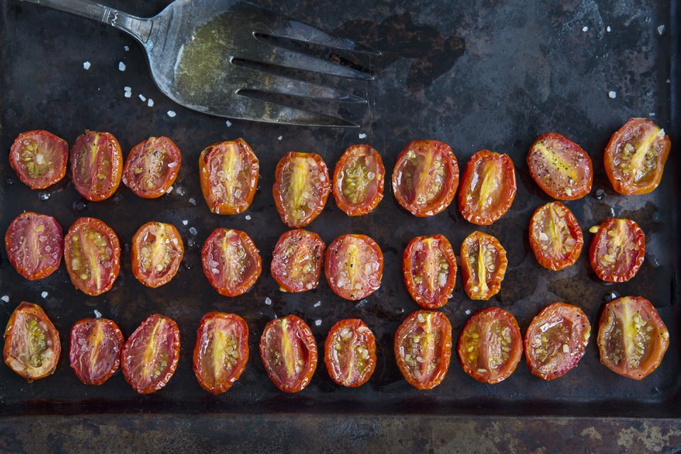 Overhead view of rows of halved roasted tomatoes on baking tin