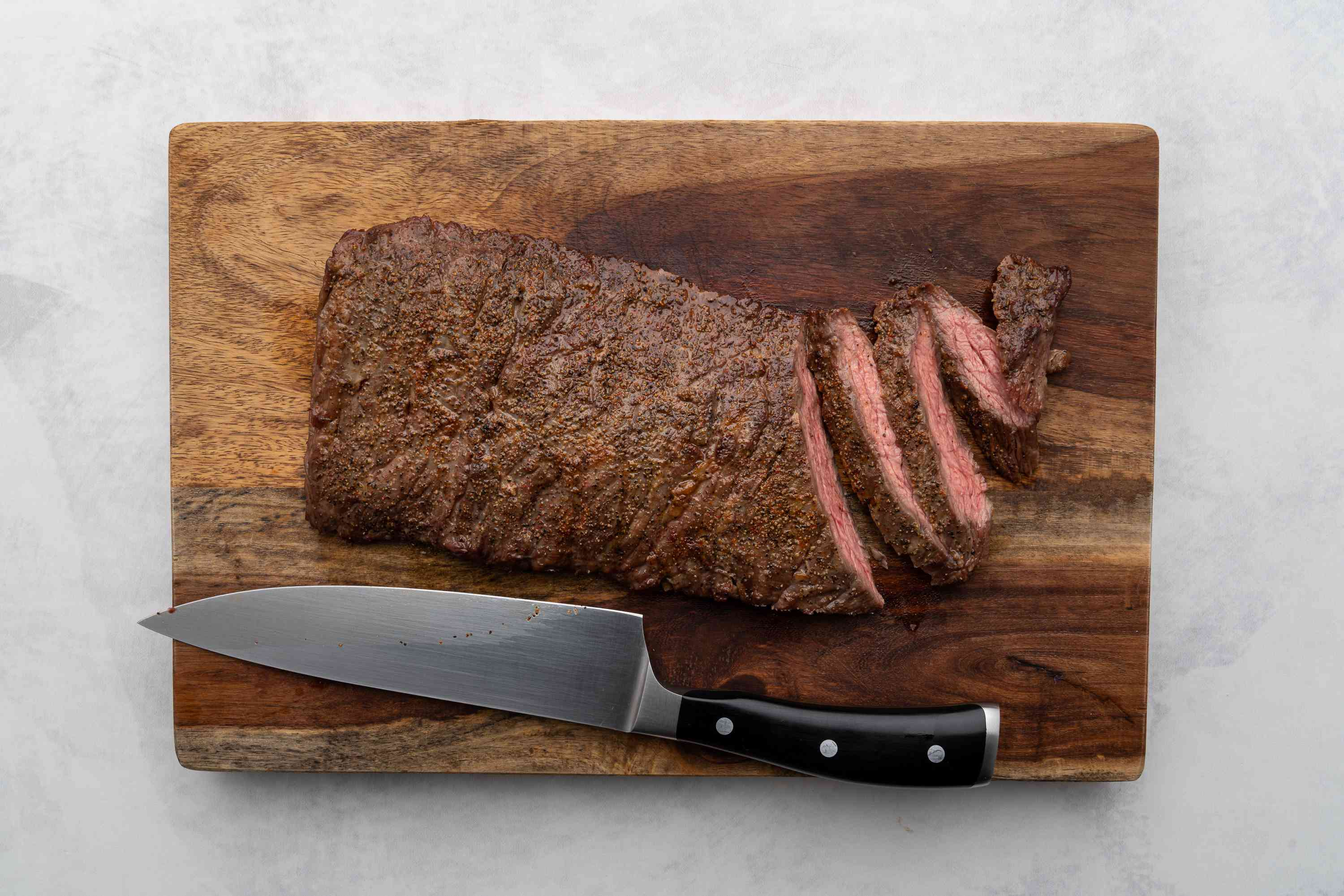 steak on cutting board with a few slices and knife resting on board