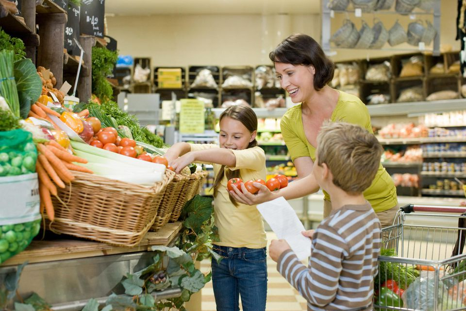 Mother and children in fruit and vegetable section of supermarket