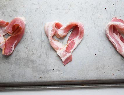 Bacon shaped like hearts on tray.