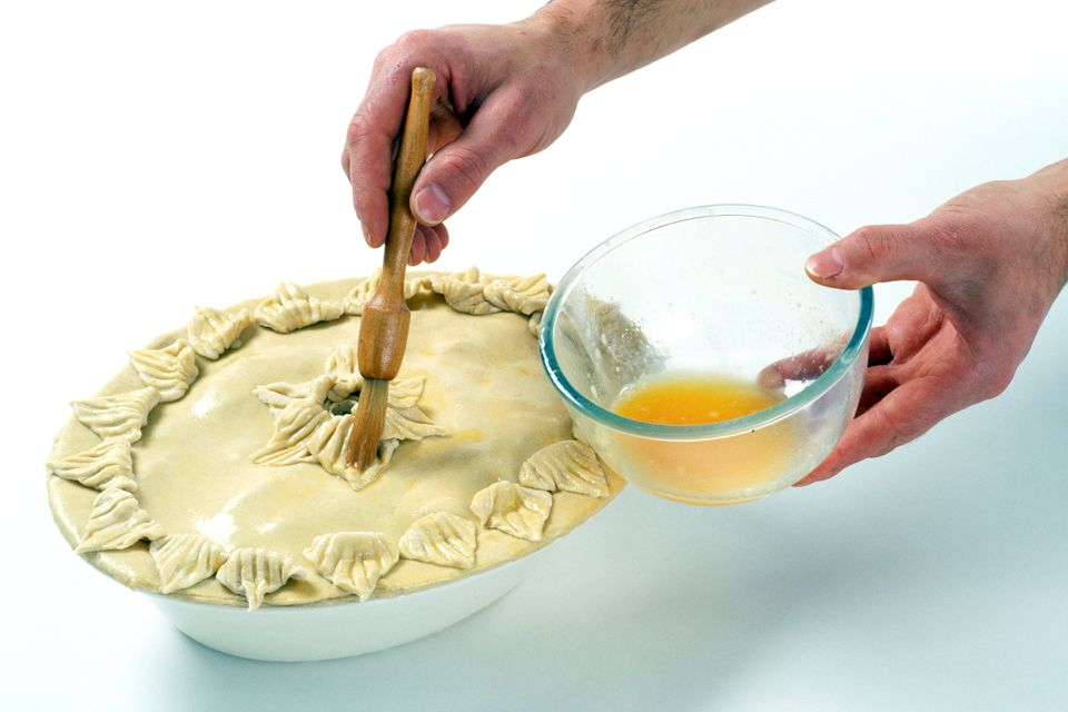 Brushing a pie crust with egg wash