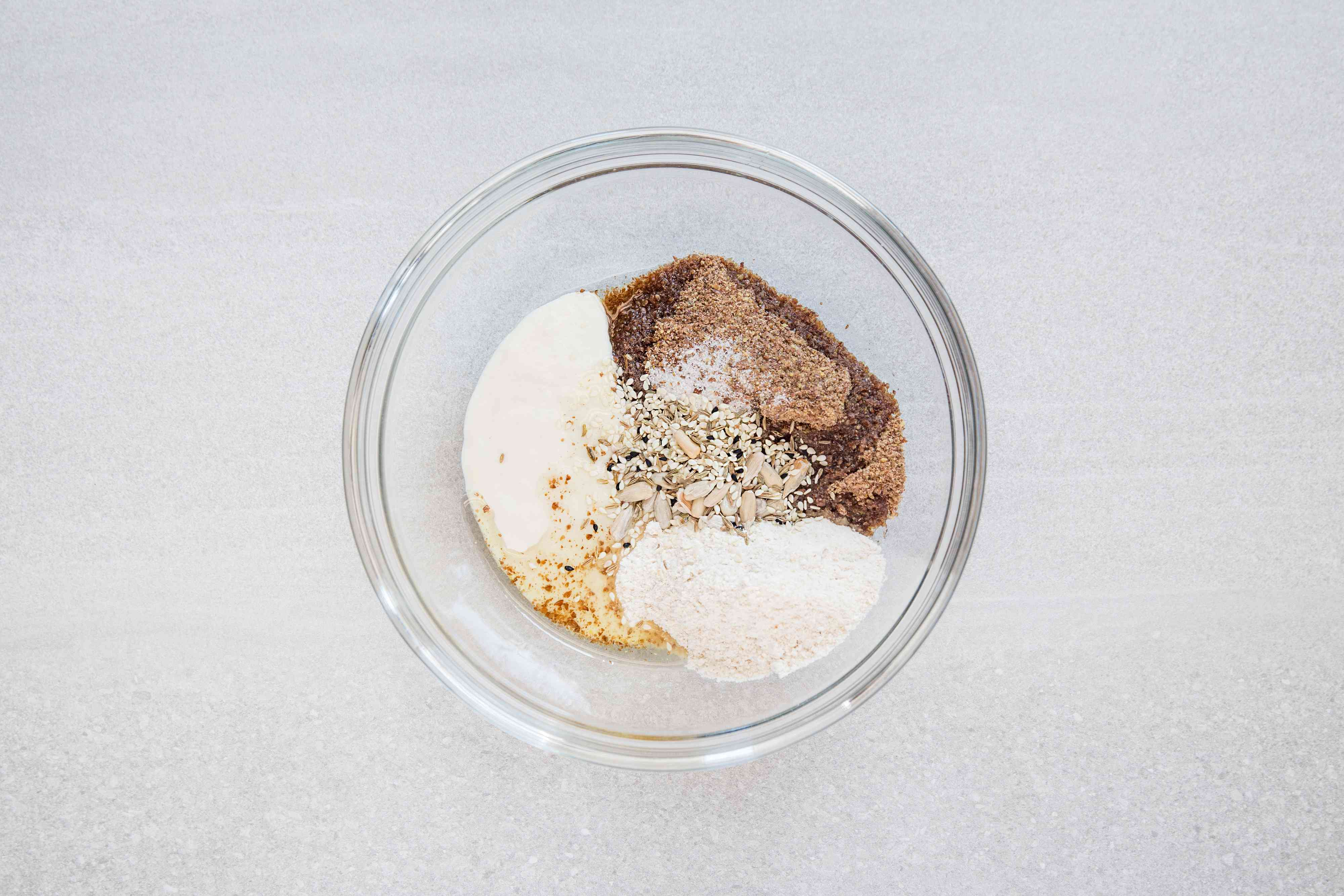 Starter, flour, flaxseed meal, oil, salt, and seeds in a bowl