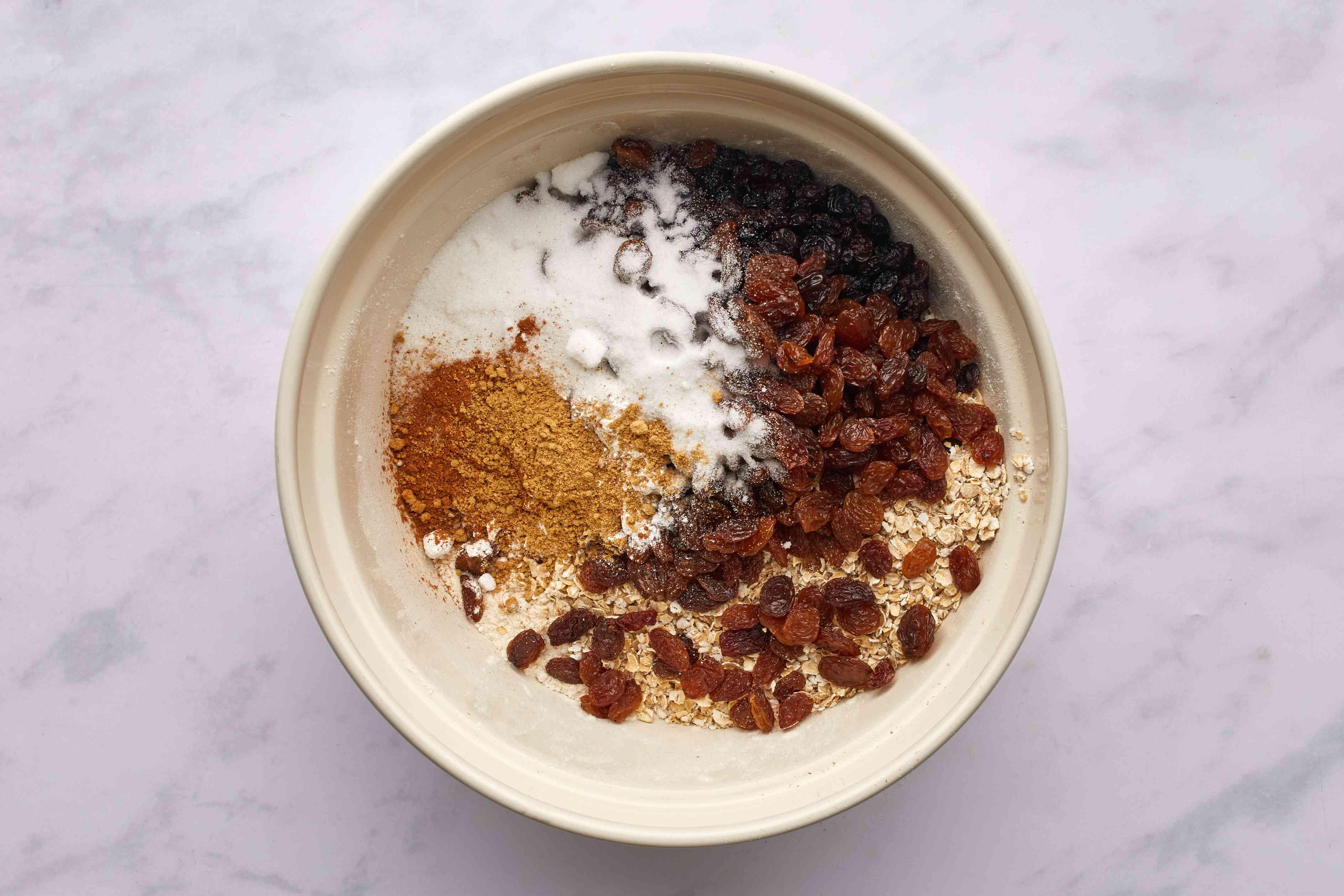 oatmeal, sultanas, dried currants, sugar, baking powder, ginger, flour and cinnamon in a bowl