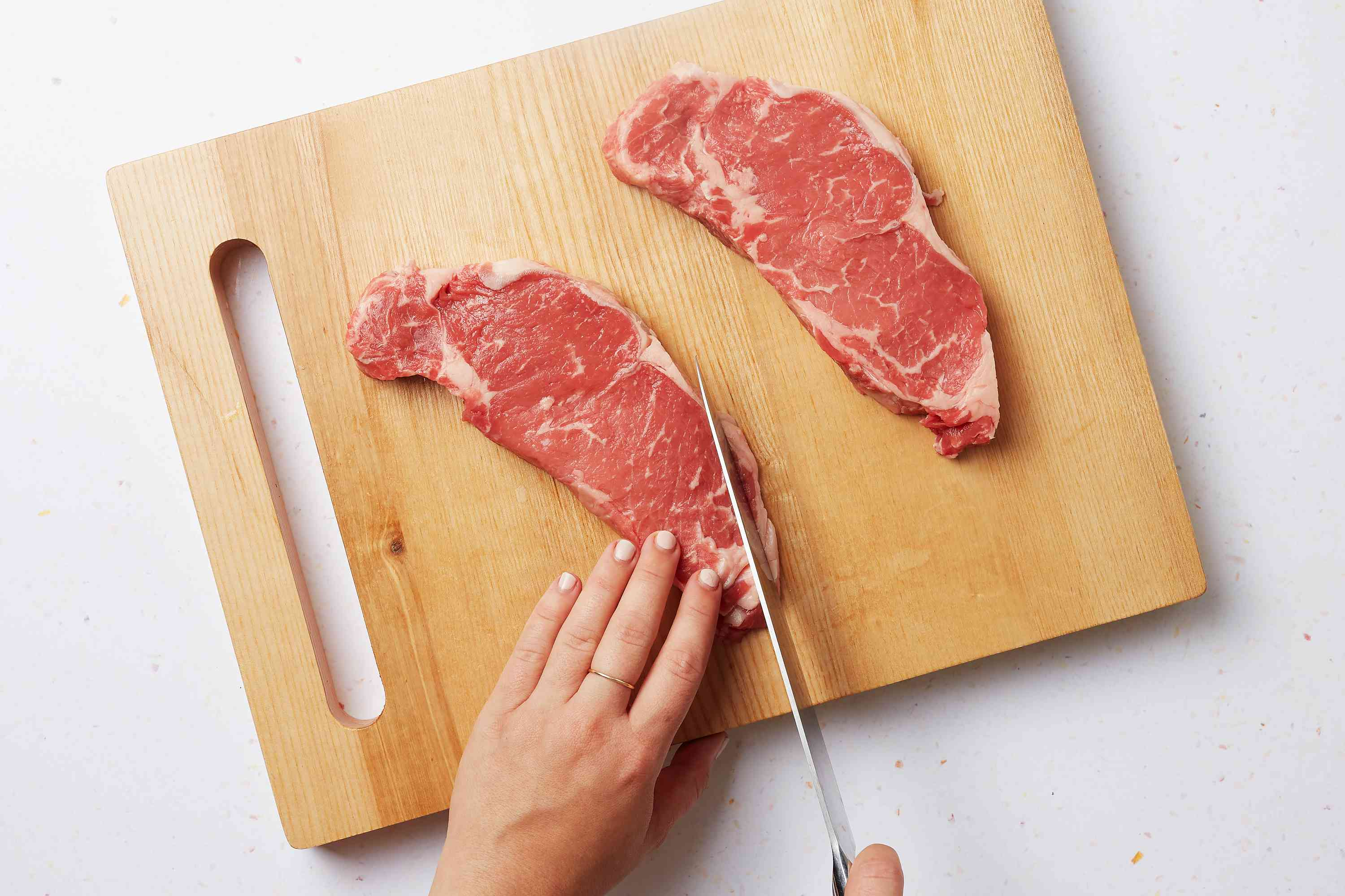 trim fat from the steaks on a cutting board