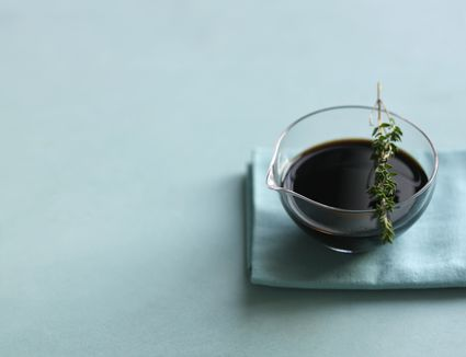 Balsamic vinegar in glass bowl, with sprig of thyme on top, on napkin