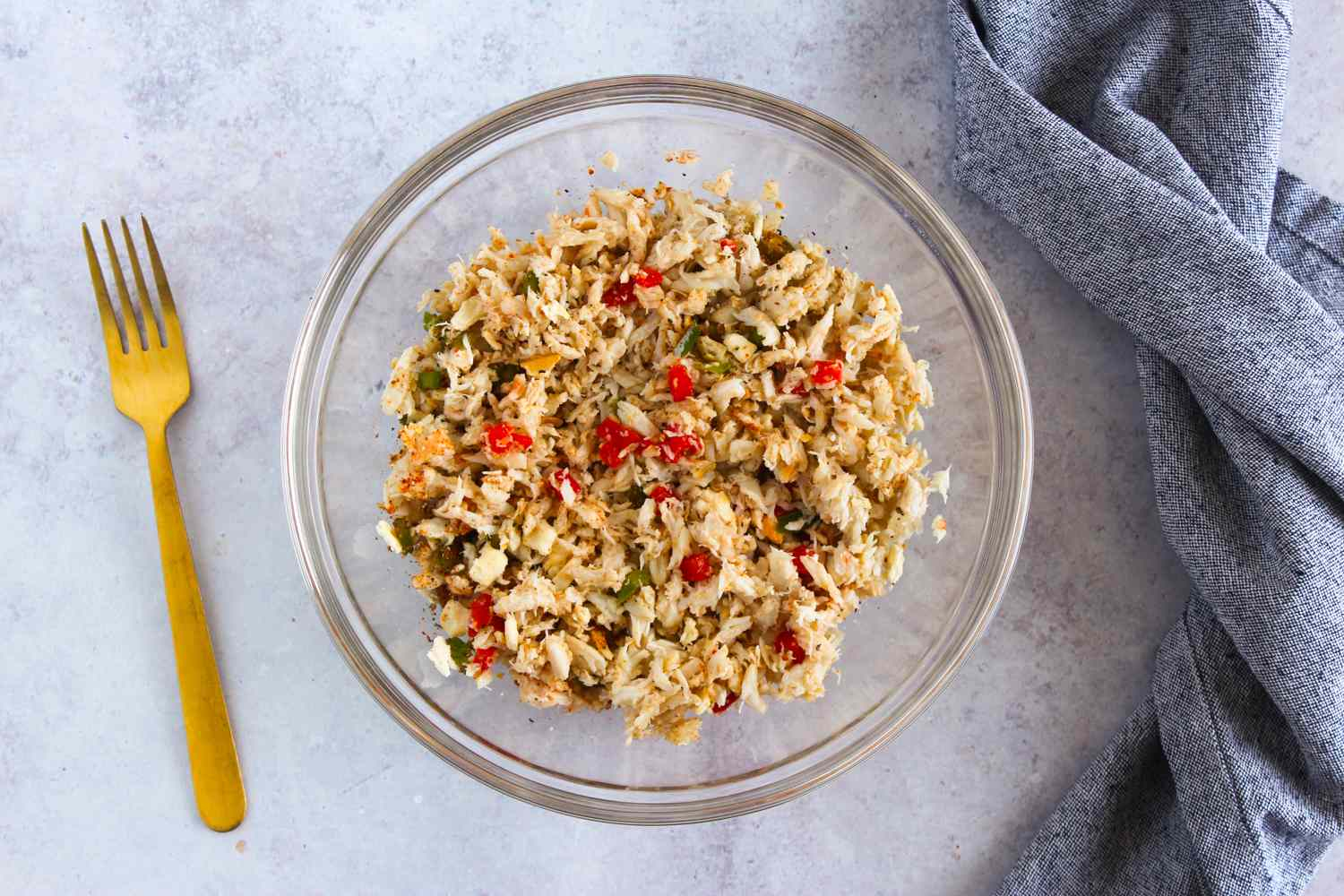 Bowl containing crabmeat, bell pepper, seasonings, and crushed crackers