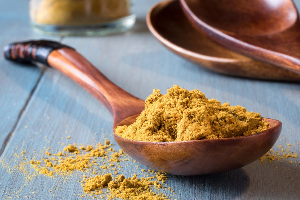 close up of curry powder on wooden spoon