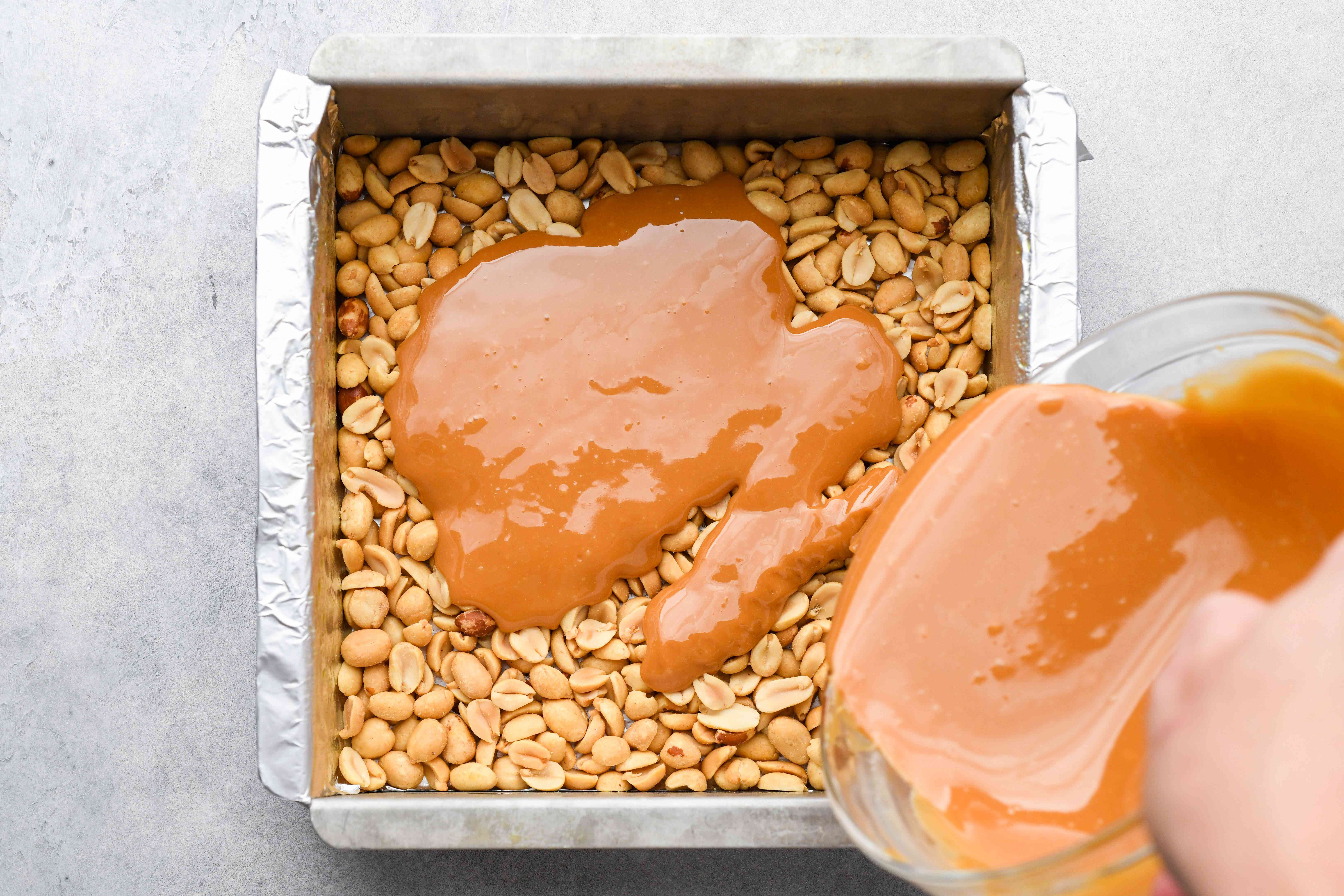 Pour the caramel over the peanuts in the pan