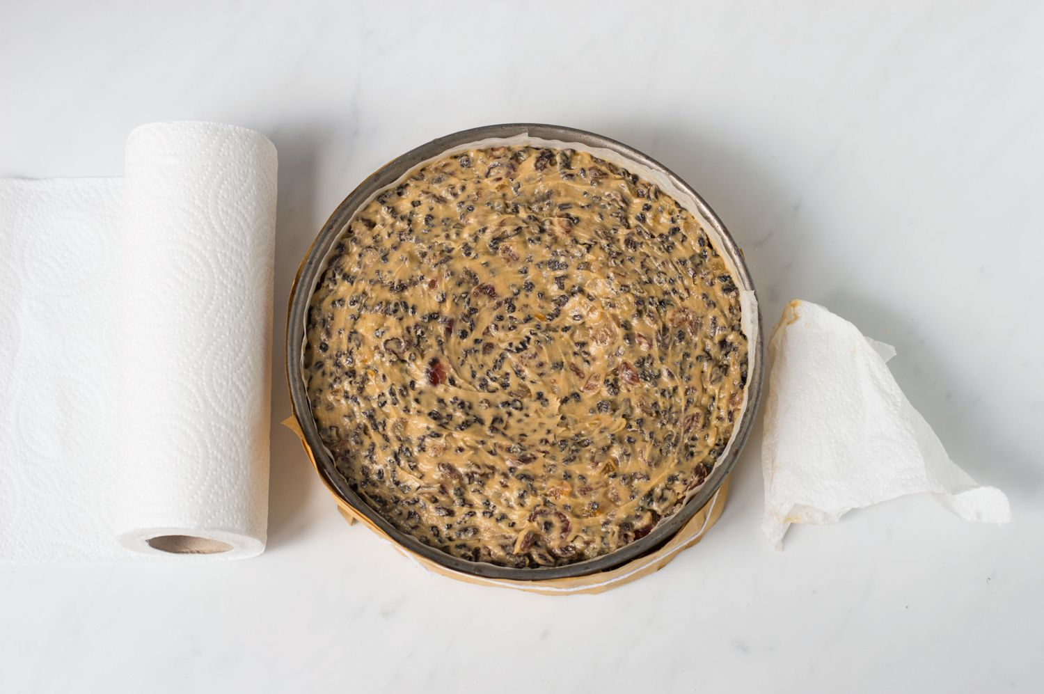 Christmas cake in pan with paper towels to remove excess batter