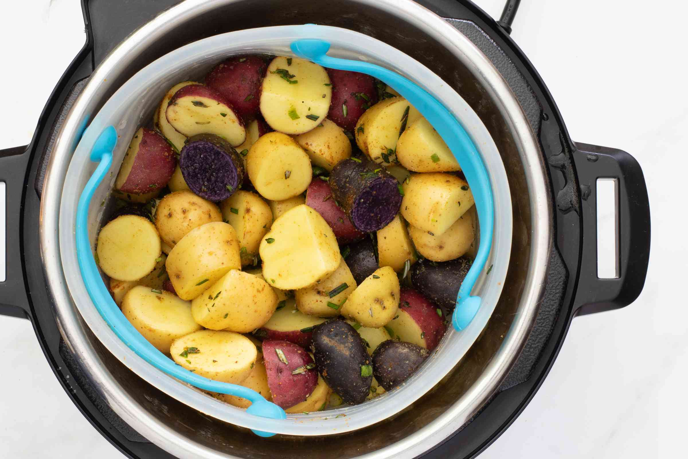 Multicolored sliced potatoes in a steaming basket in the Instant Pot