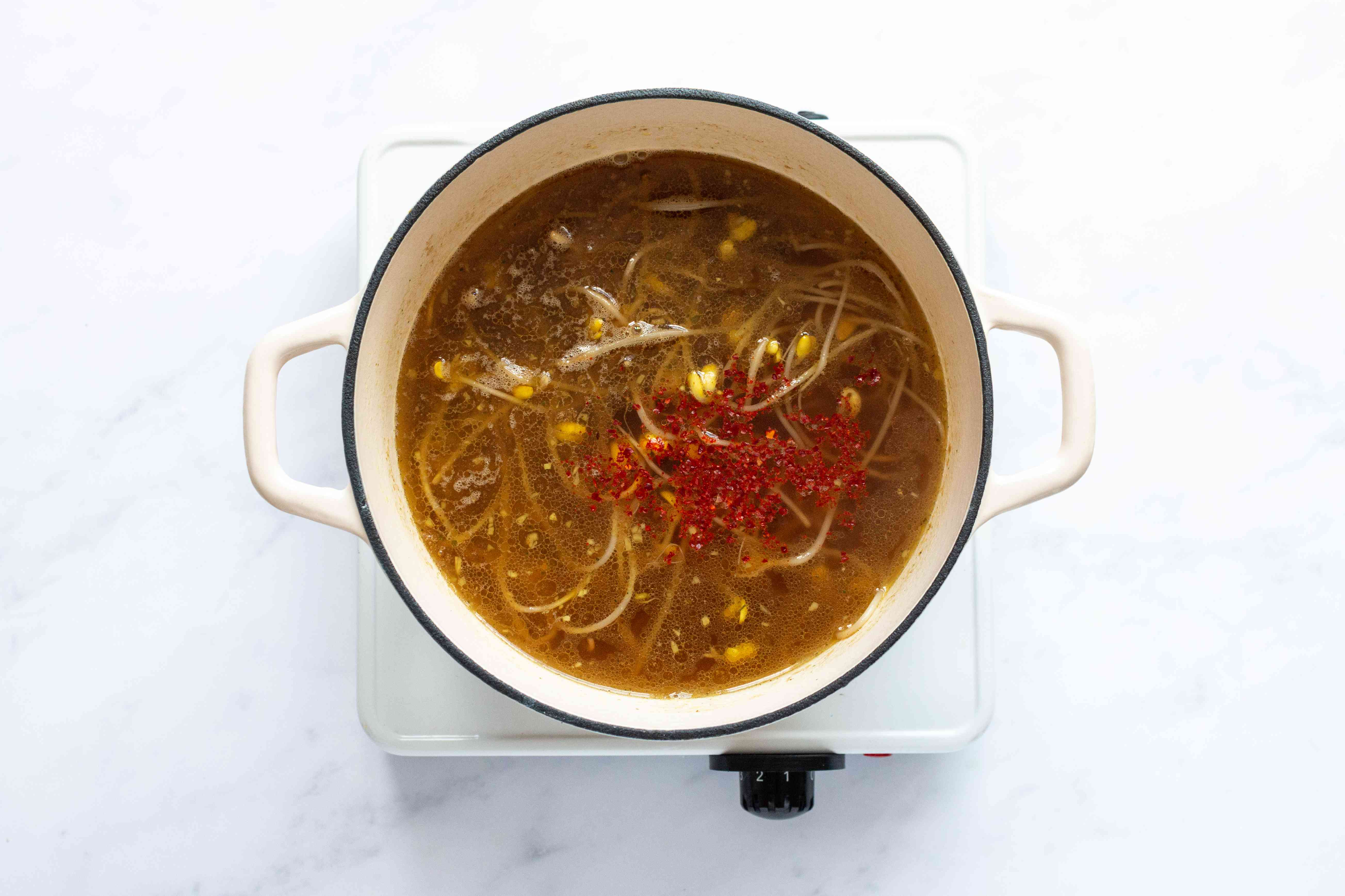 soup and red peppers cooking in a pot