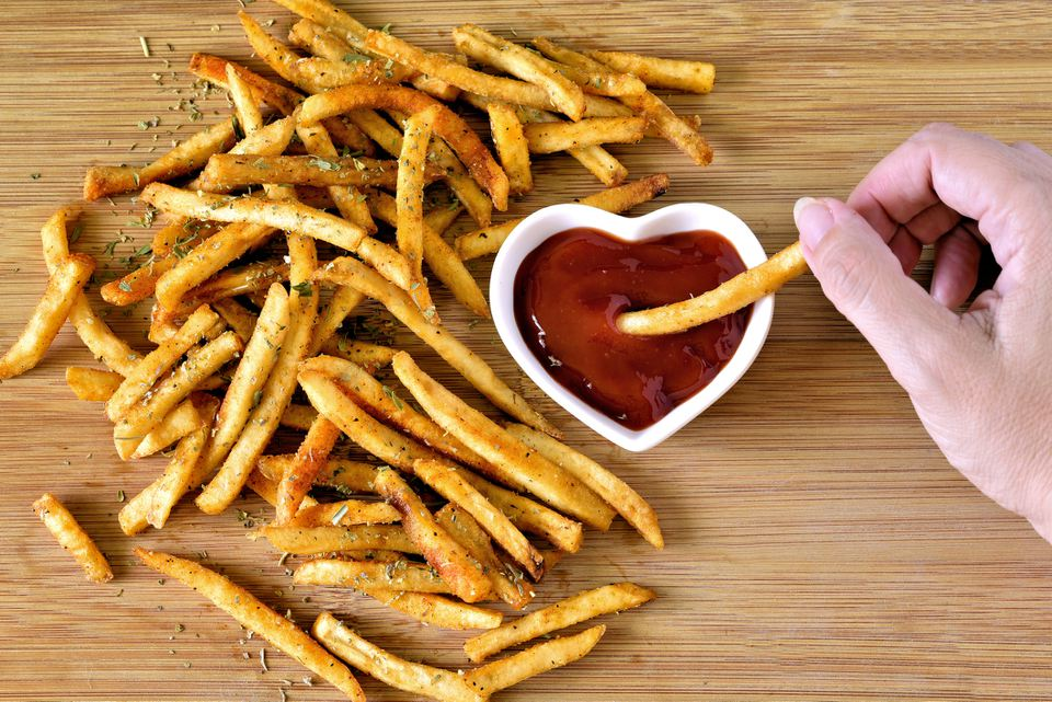 Crispy french fries being dipped in ketchup