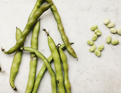 Fava beans lying on marble kitchen countertop