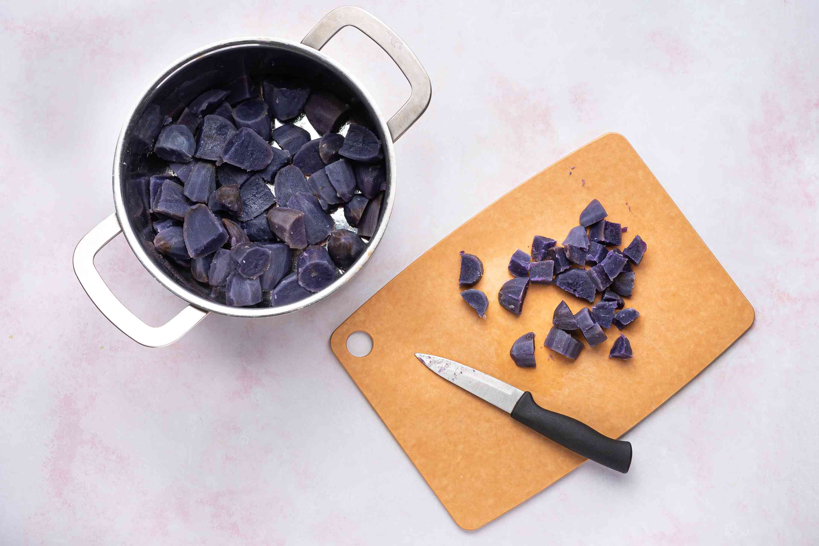 purple potatoes cut into small pieces on a cutting board