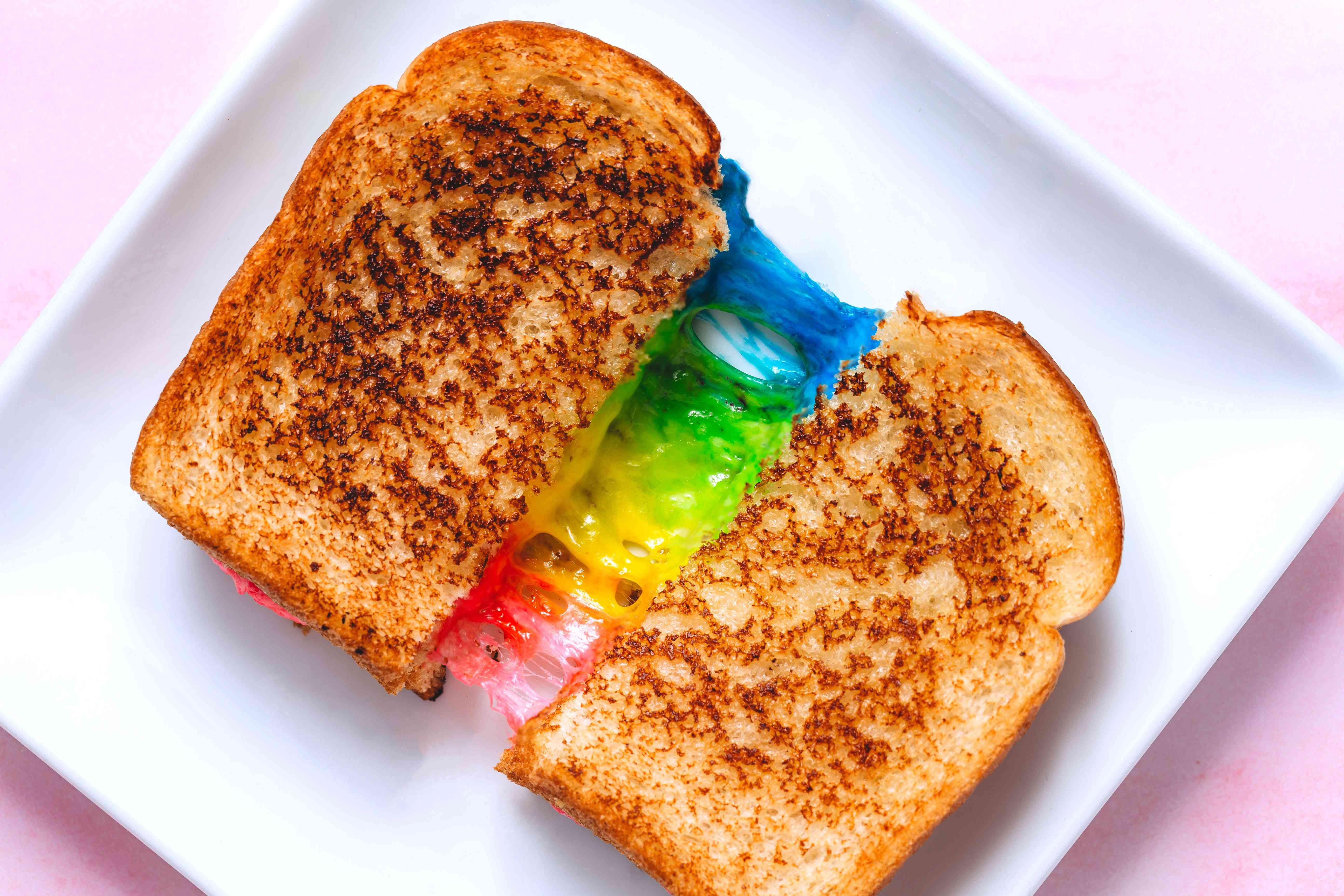 rainbow grilled cheese cut in half, on a plate, pulled apart to reveal blue, green, yellow, and pink cheese