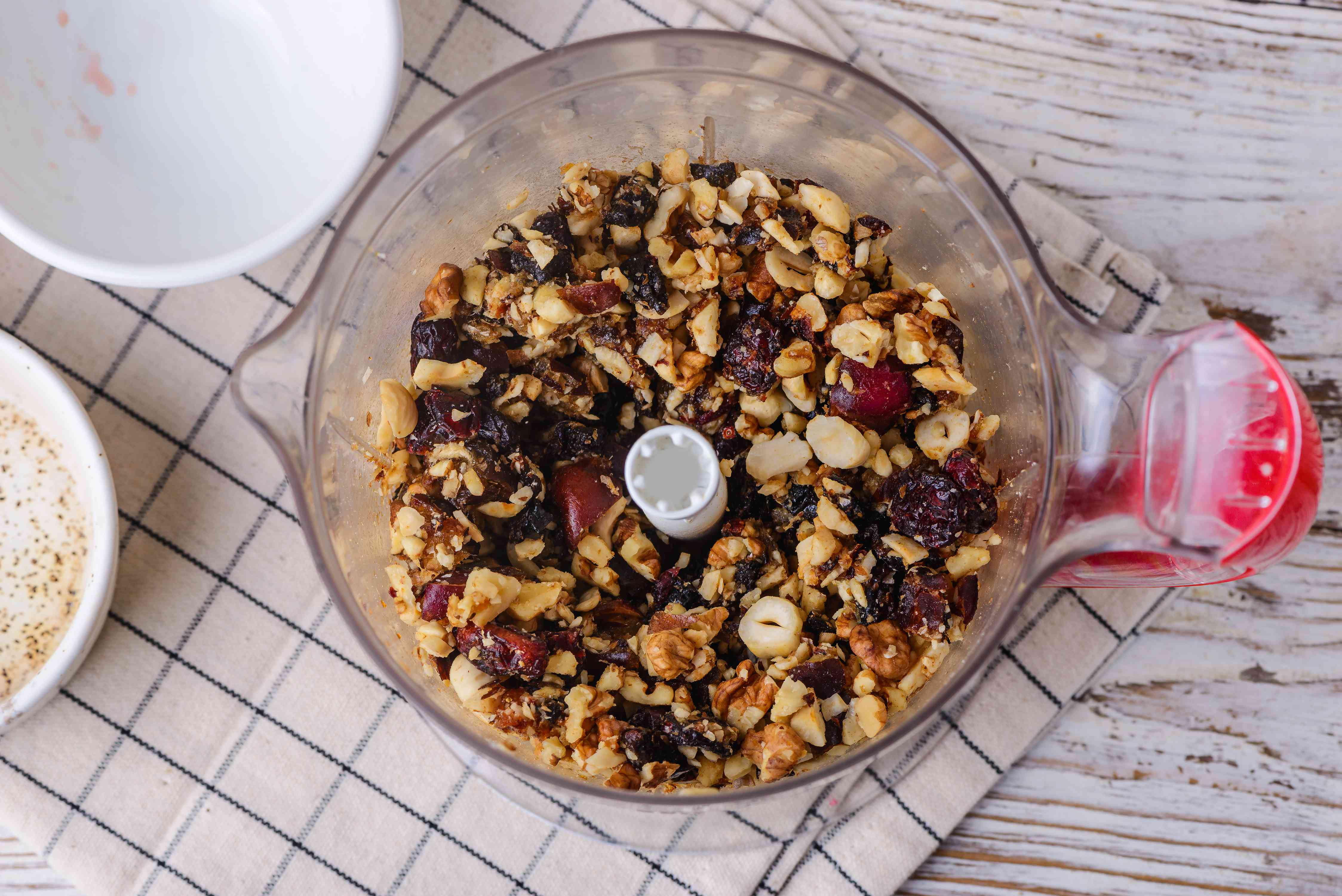 Place dates, walnuts, cranberries, prunes, and hazelnuts in food processor