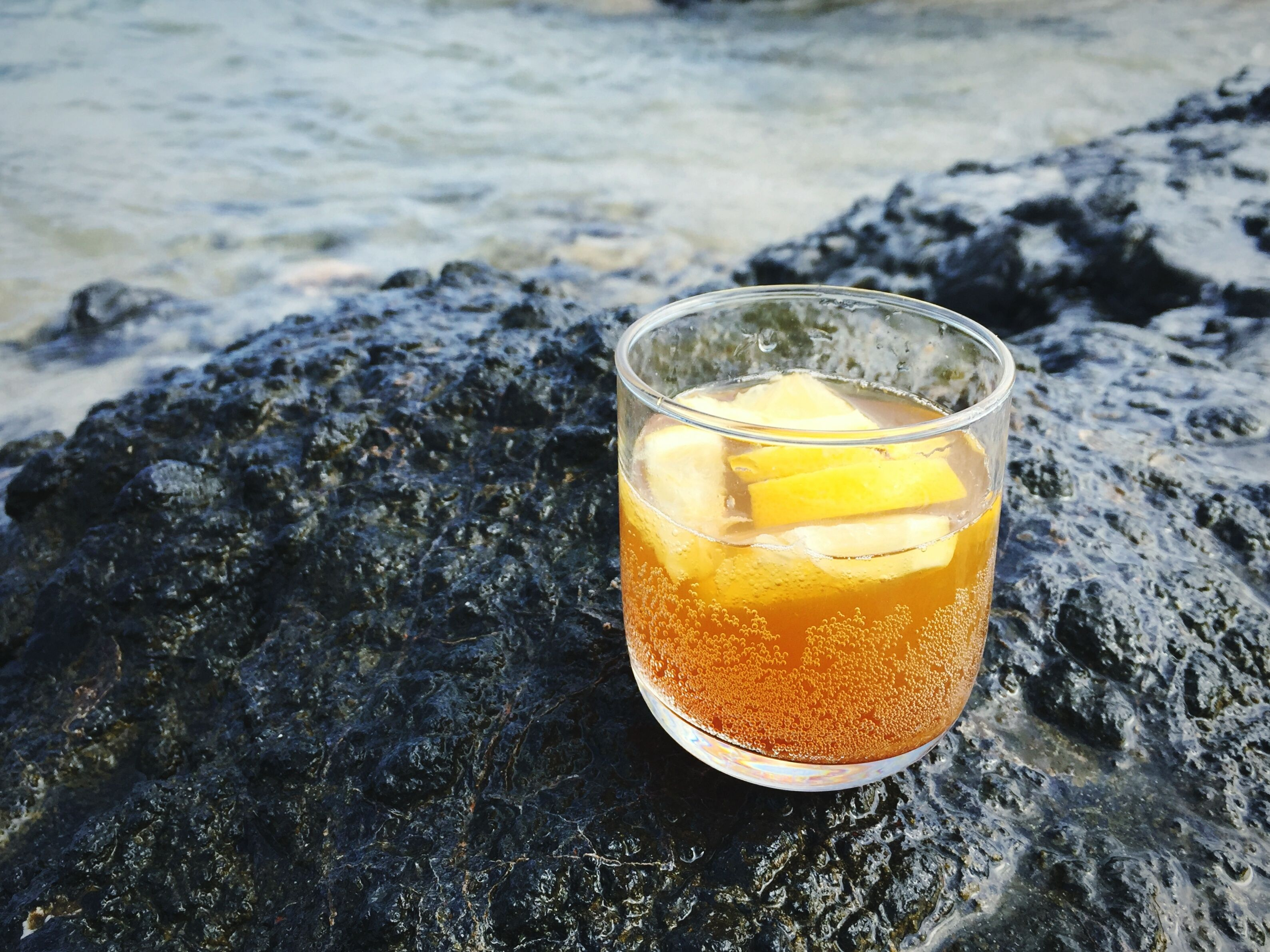 High Angle View Of Glass With Drink On Rock By Sea