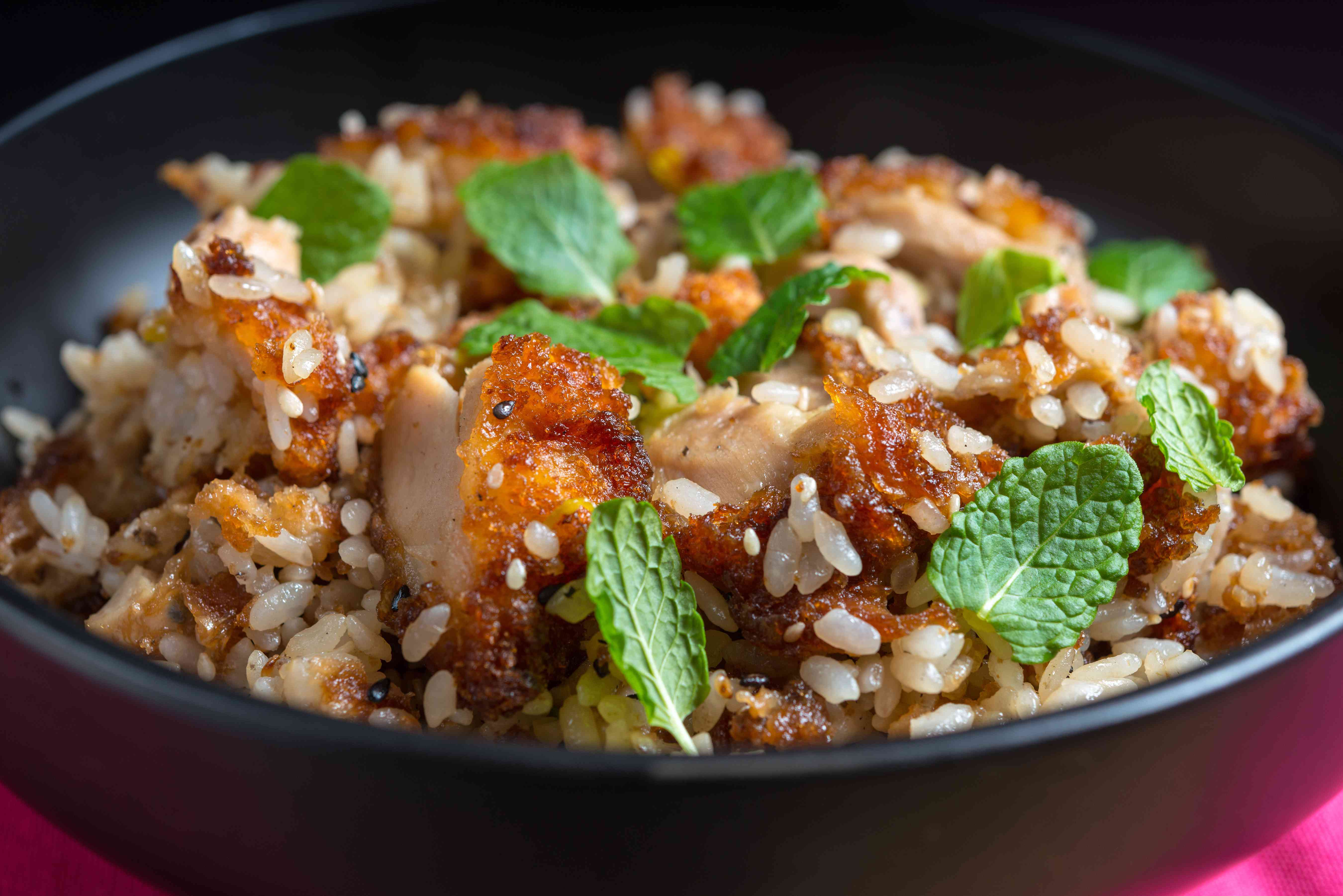 Close-Up Of Fried Rice With Chicken Meat And Mint Leaves In Bowl