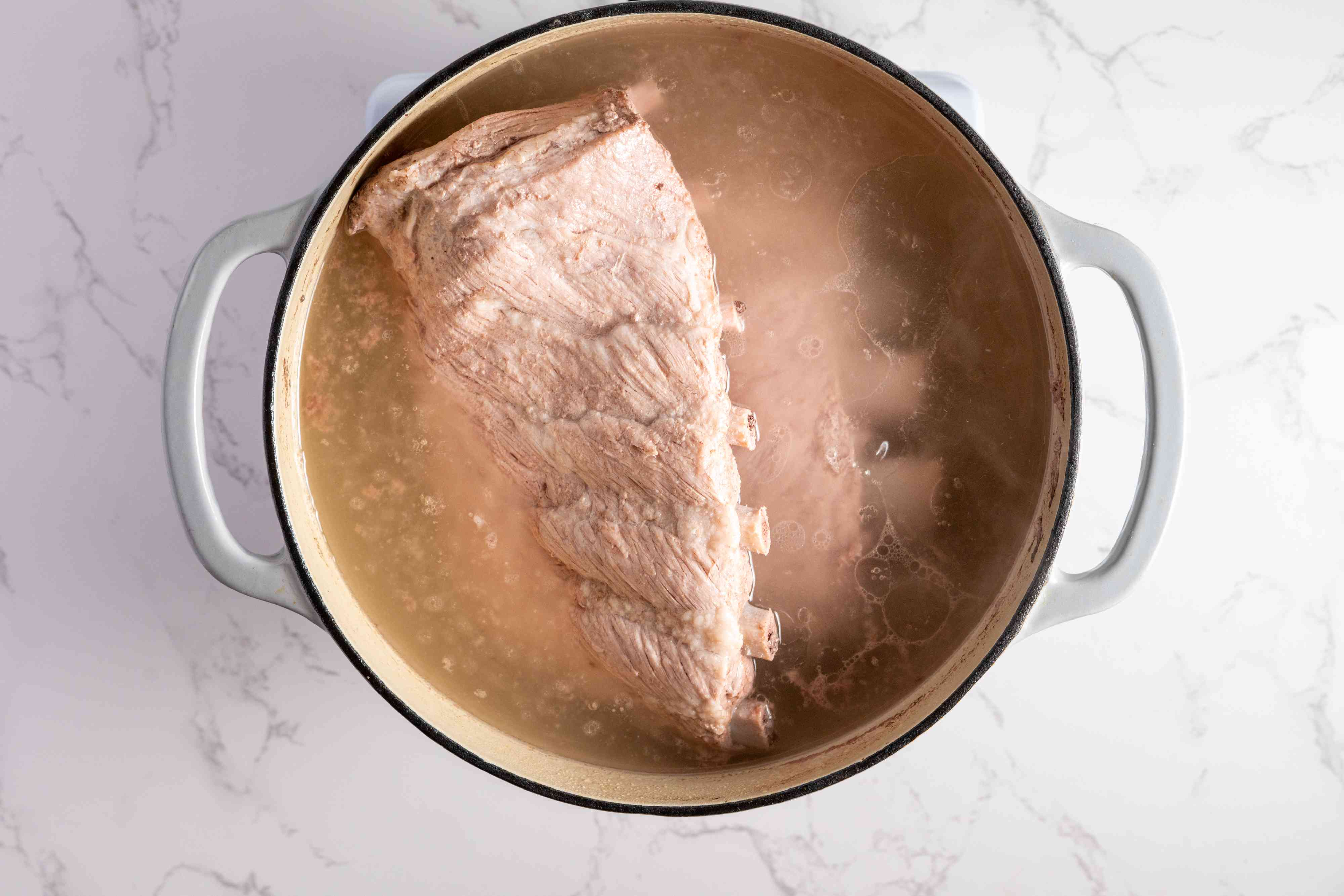 spareribs cooking in a pot with water