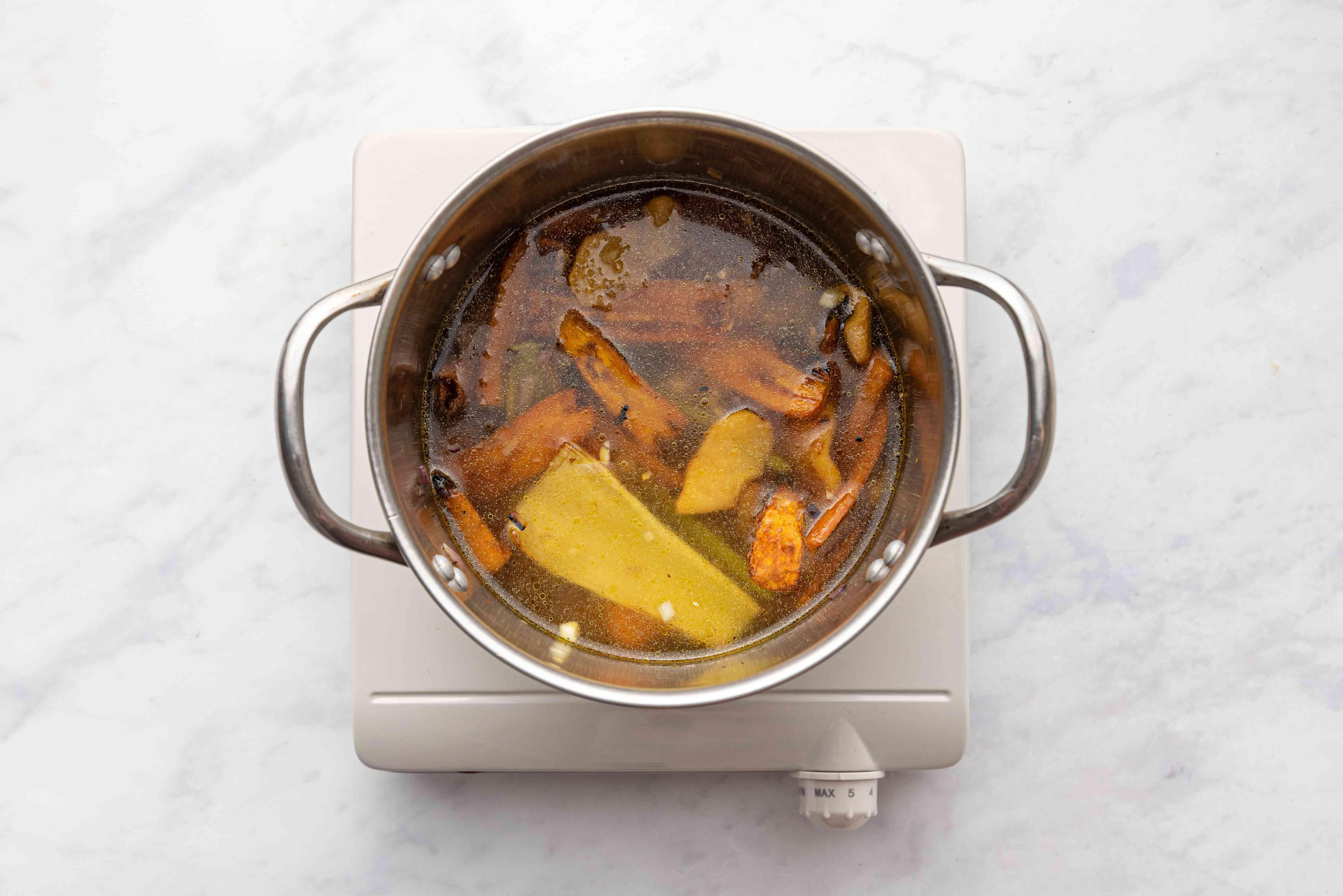 Roasted vegetables with stock in a pot