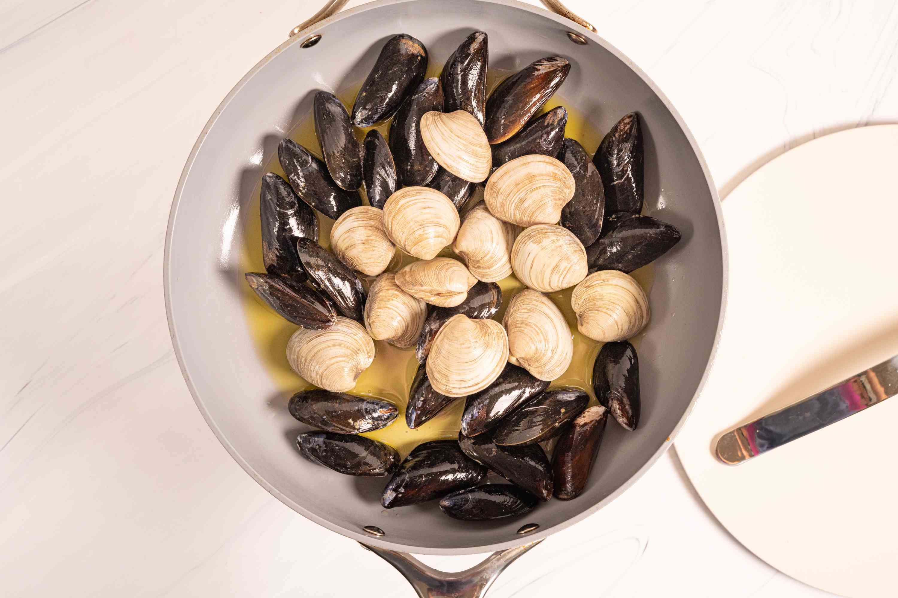 clams and muscles cooking in a skillet