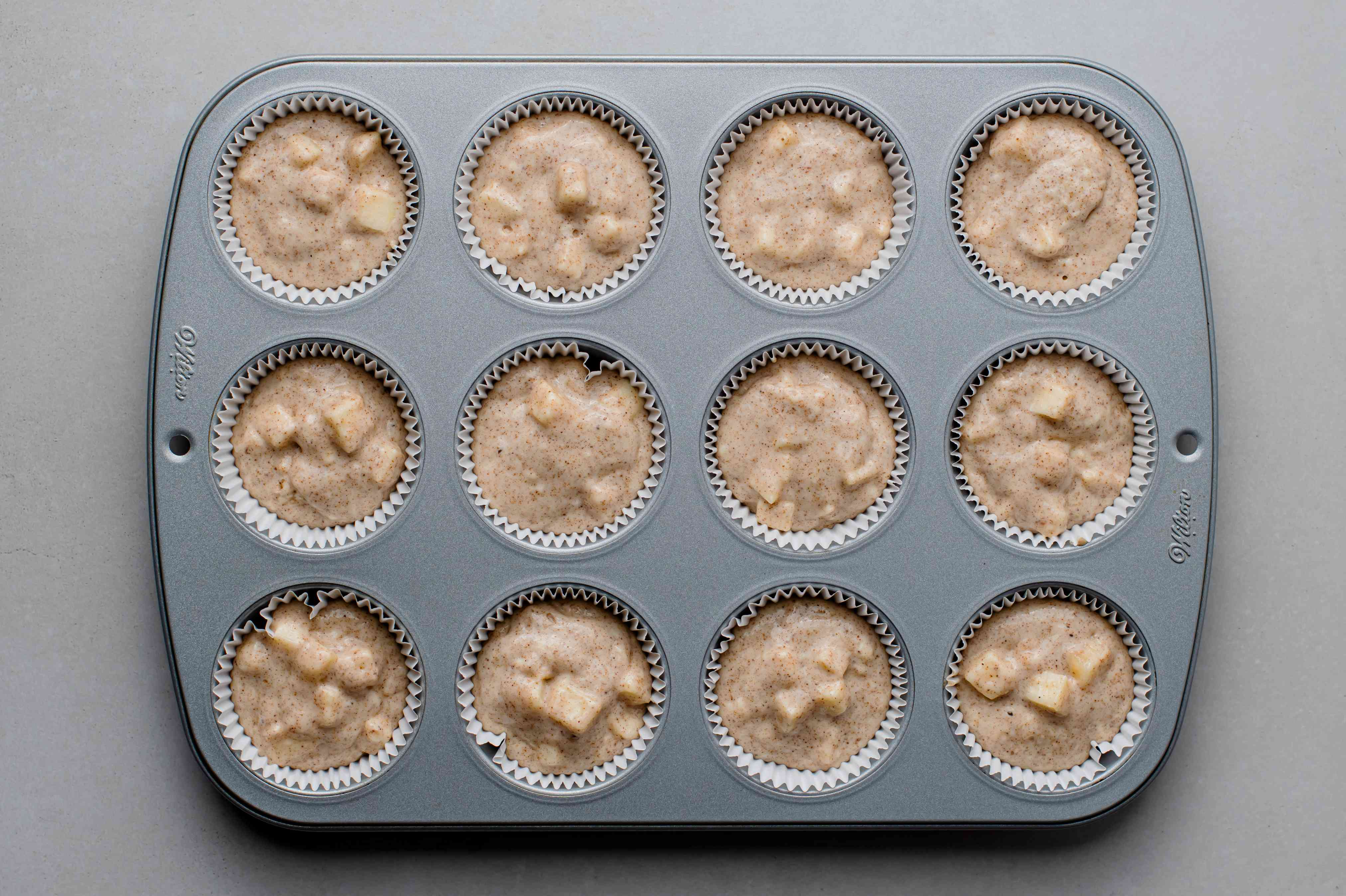 apple cinnamon muffin batter in paper-lined muffin tins