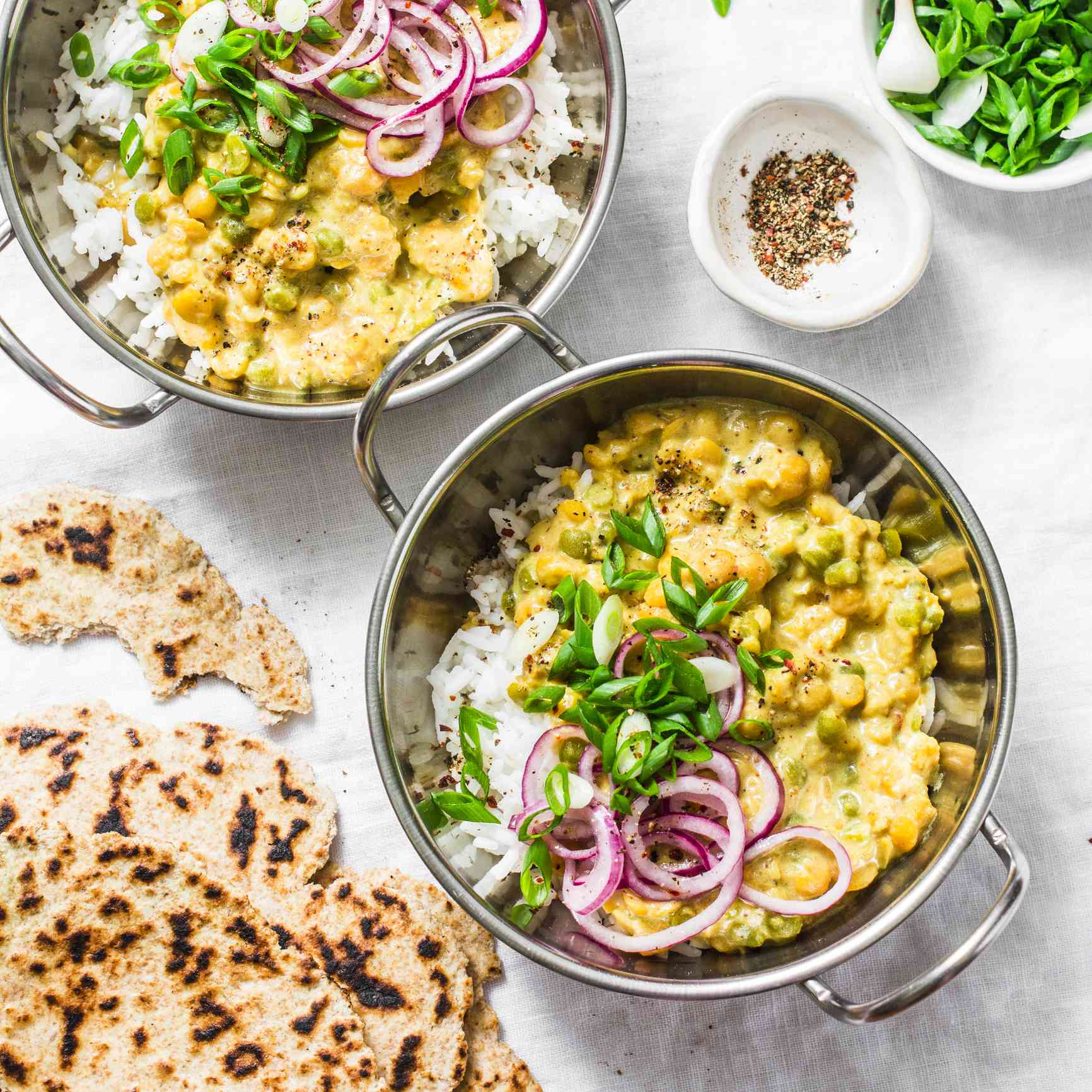Indian dhal with jasmine rice, marinated red onion, scallion and whole grain flatbread on light background, top view. Flat lay, vegetarian food concept